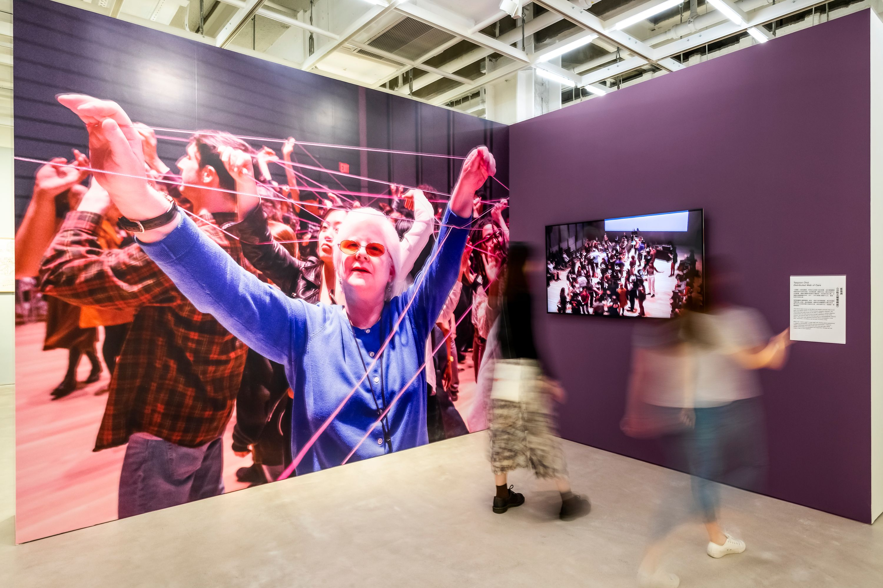 A large photo is printed on a gallery wall, showing a woman in a blue shirt holding string above her head. Other people behind her are holding onto the same string. On another gallery wall, which is painted purple, there is a video screen which two people are watching.