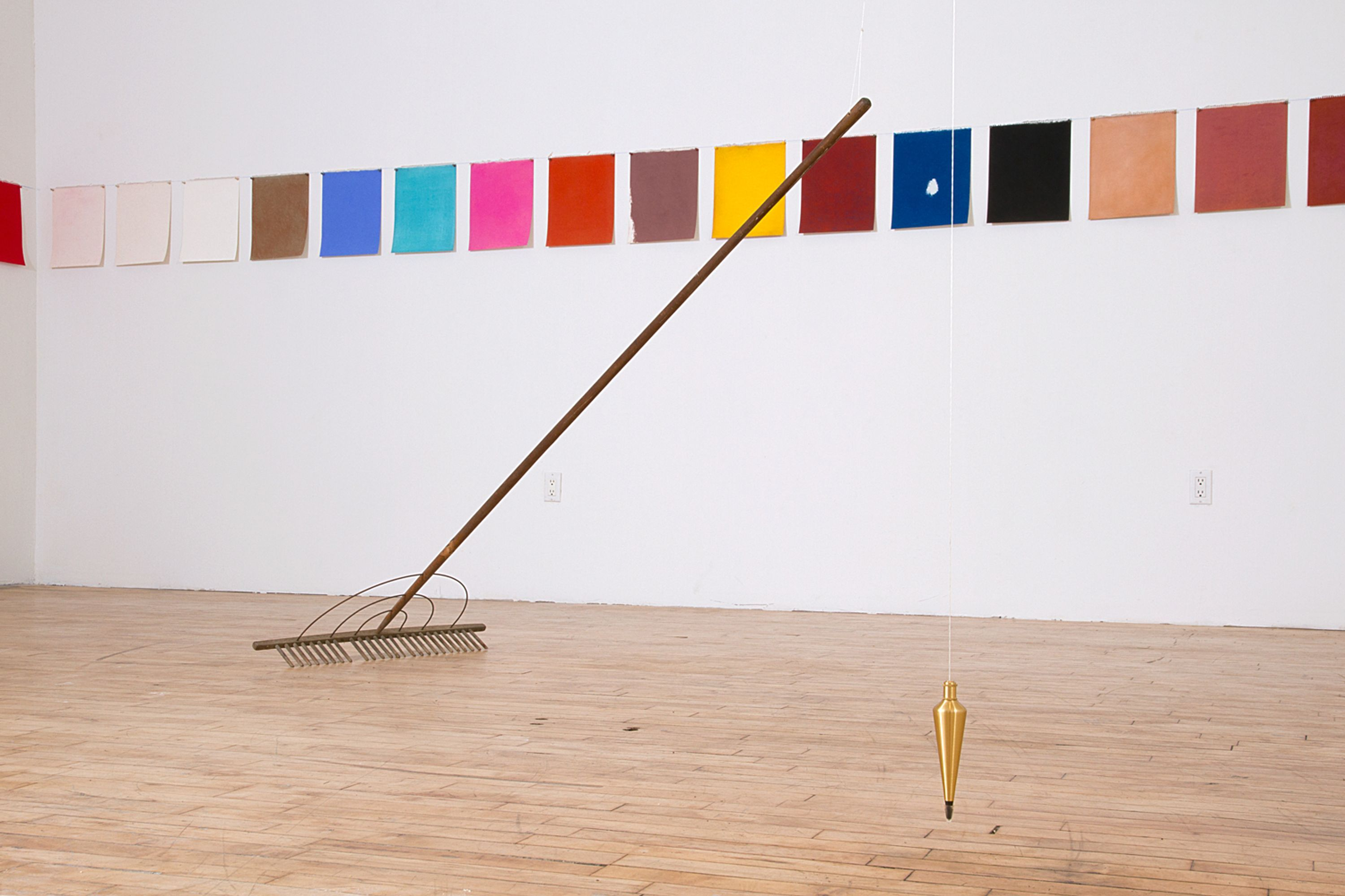 """An installation view of Kathleen White's """"A Rake's Progress,"""" which features a long row of colorful, paper sheets, and a hanging plumb and rake in the middle of the floor"""