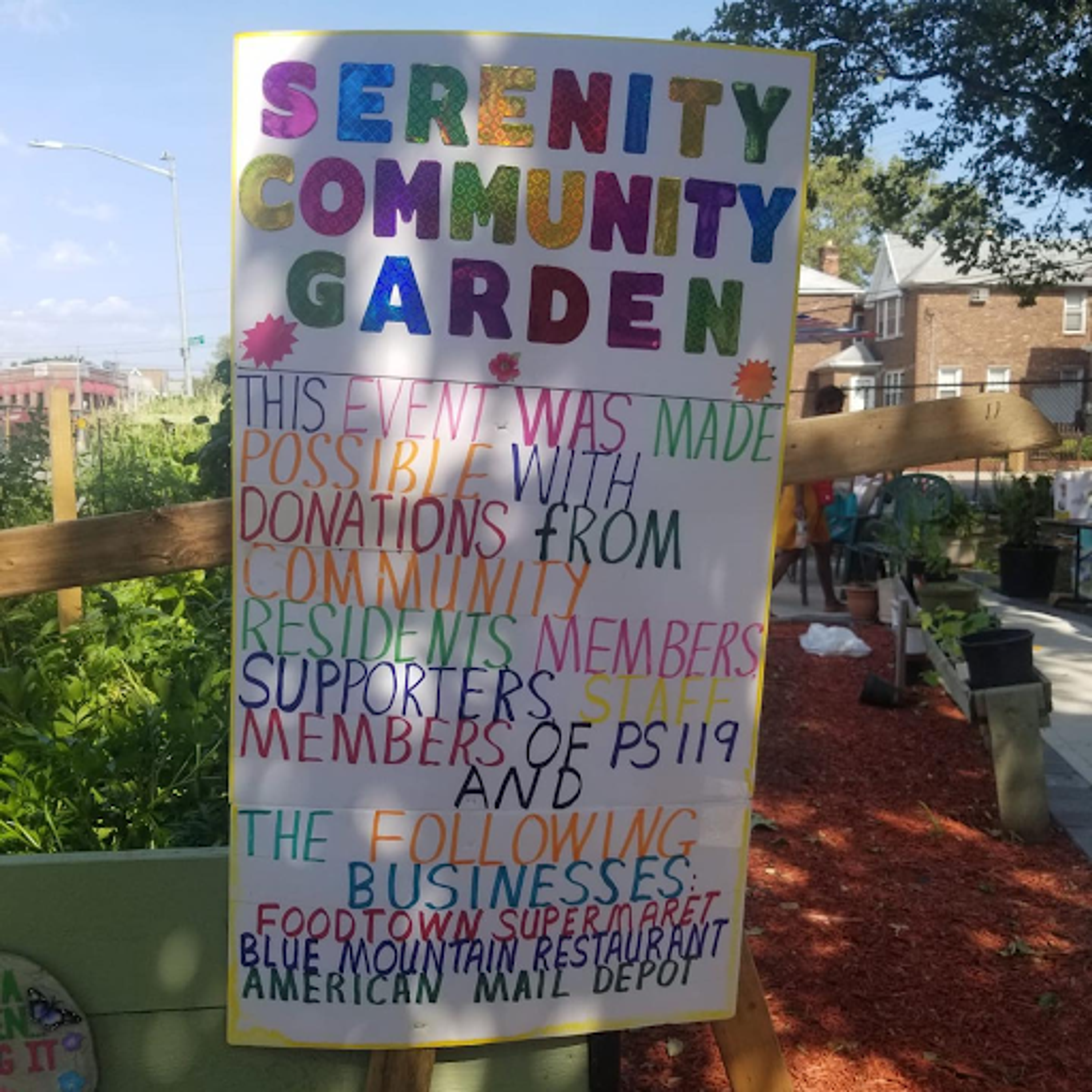 """A sign that reads """"Serenity Community Garden."""""""