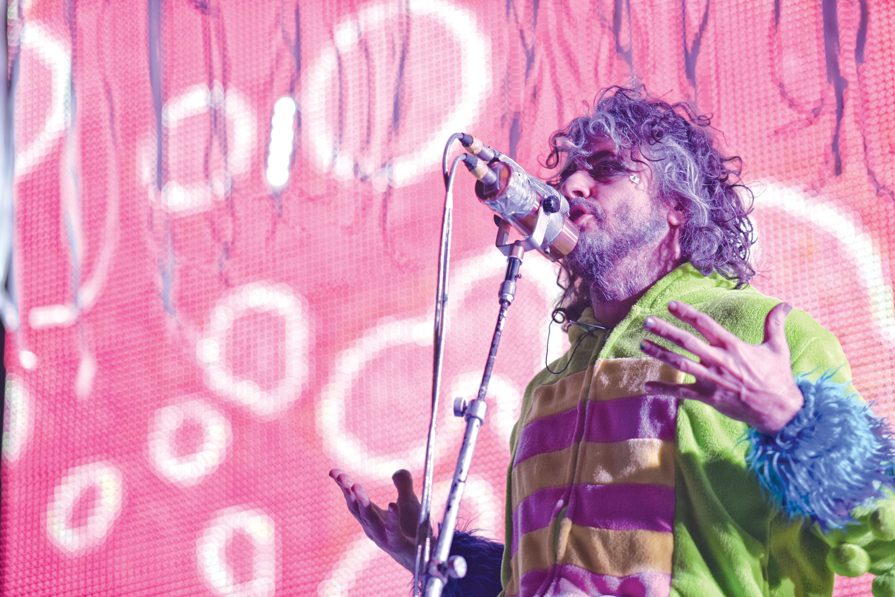 The Flaming Lips live in front of pink LED wall.