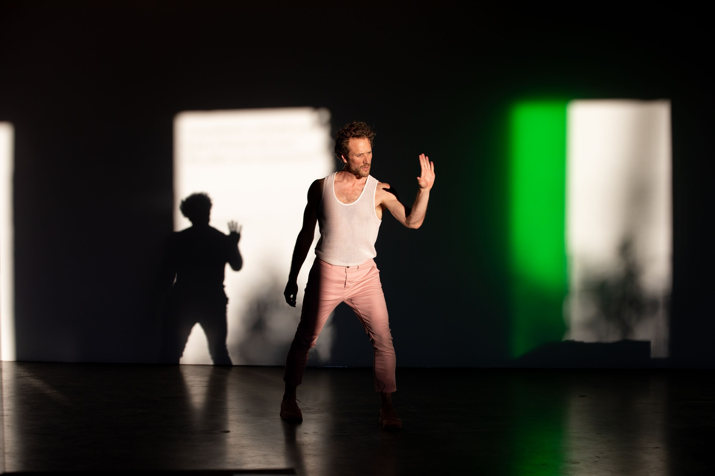 Ryan Kelly dances in CLOCKWORK, with high contrast shadows in the background.