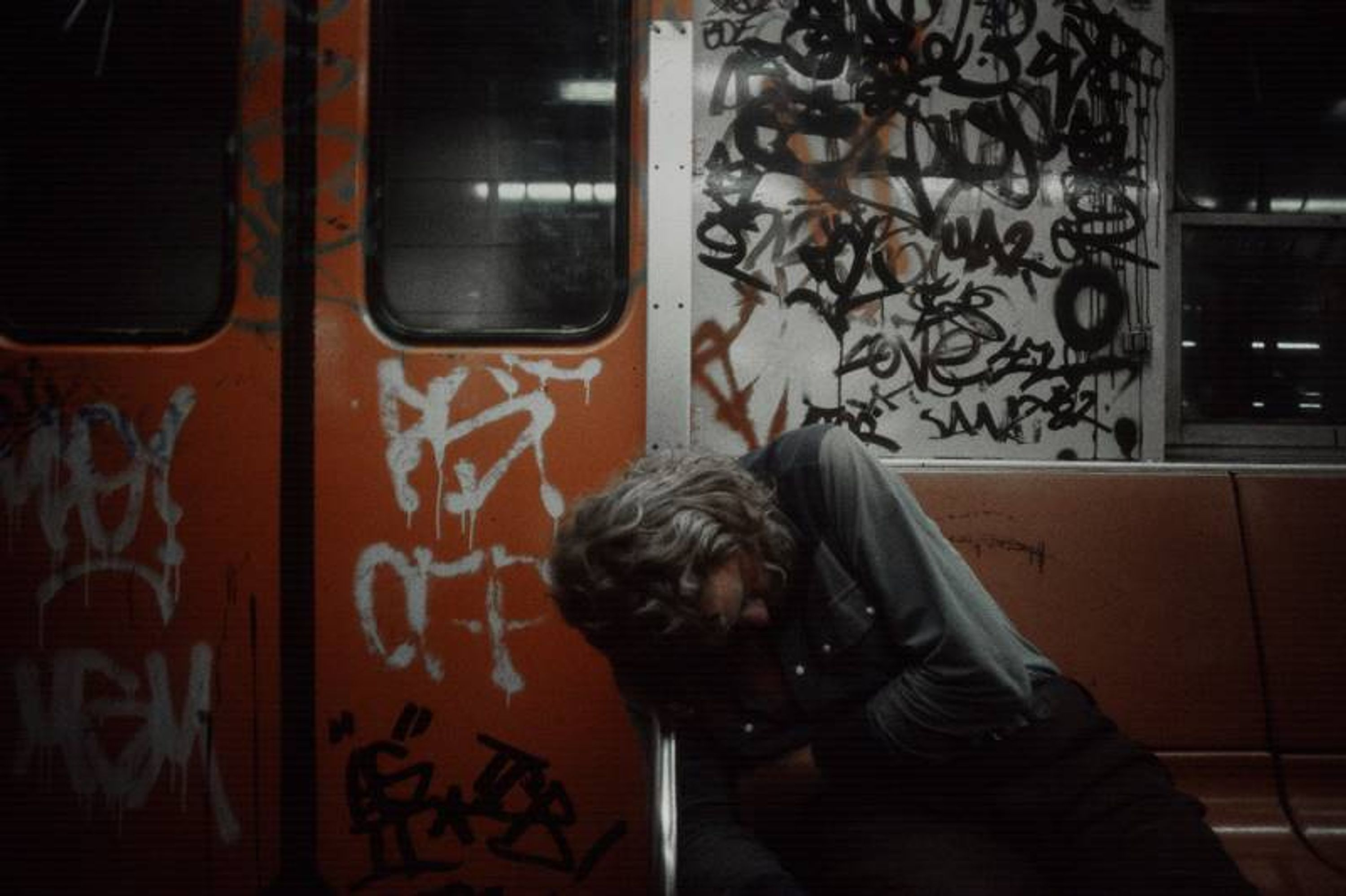 Photo of a man passed out on the subway in the 90s, the car covered with graffiti.