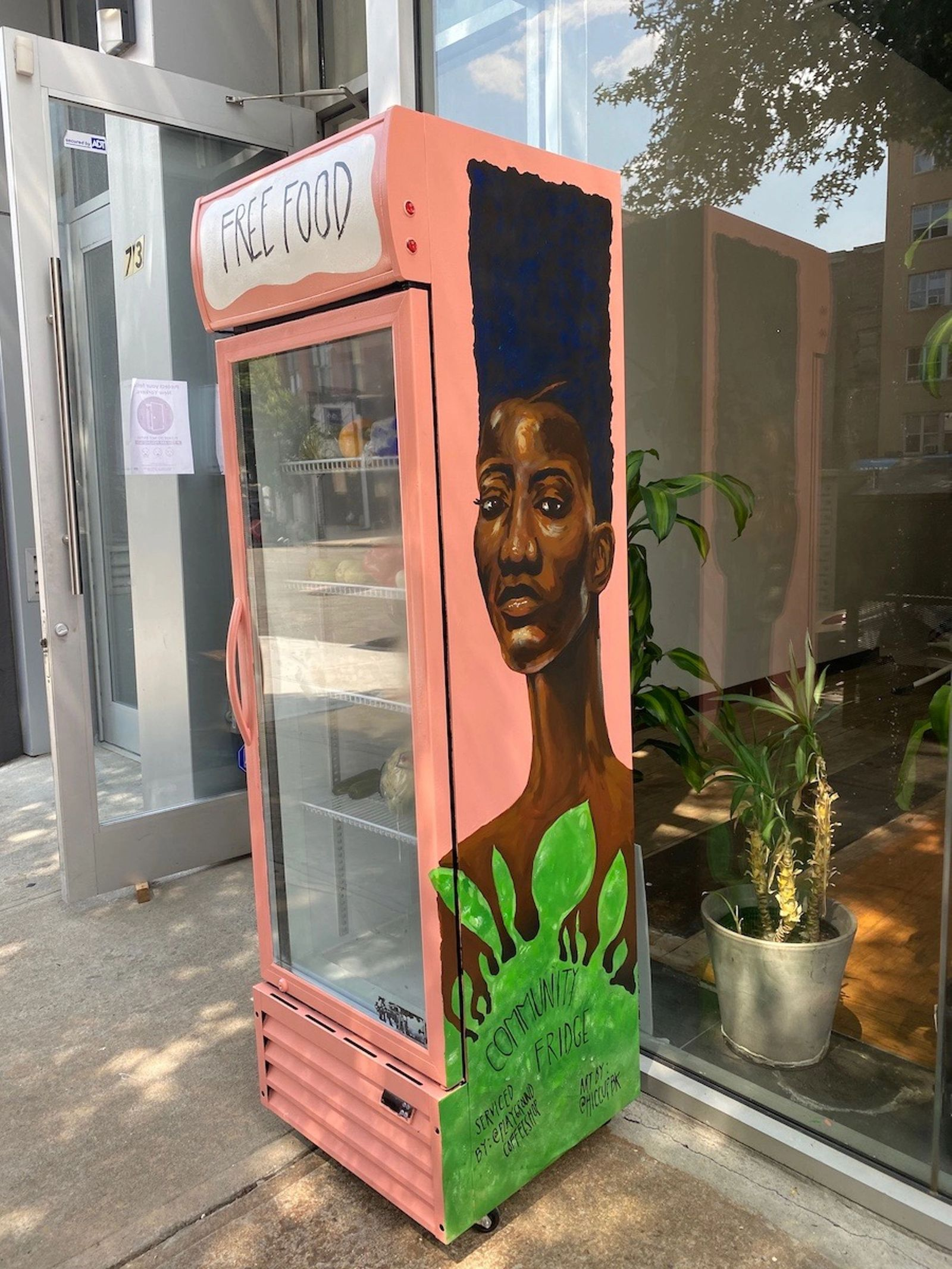 Coral-colored community fridge with striking Black woman painted on the side, outside of Beauty Strike