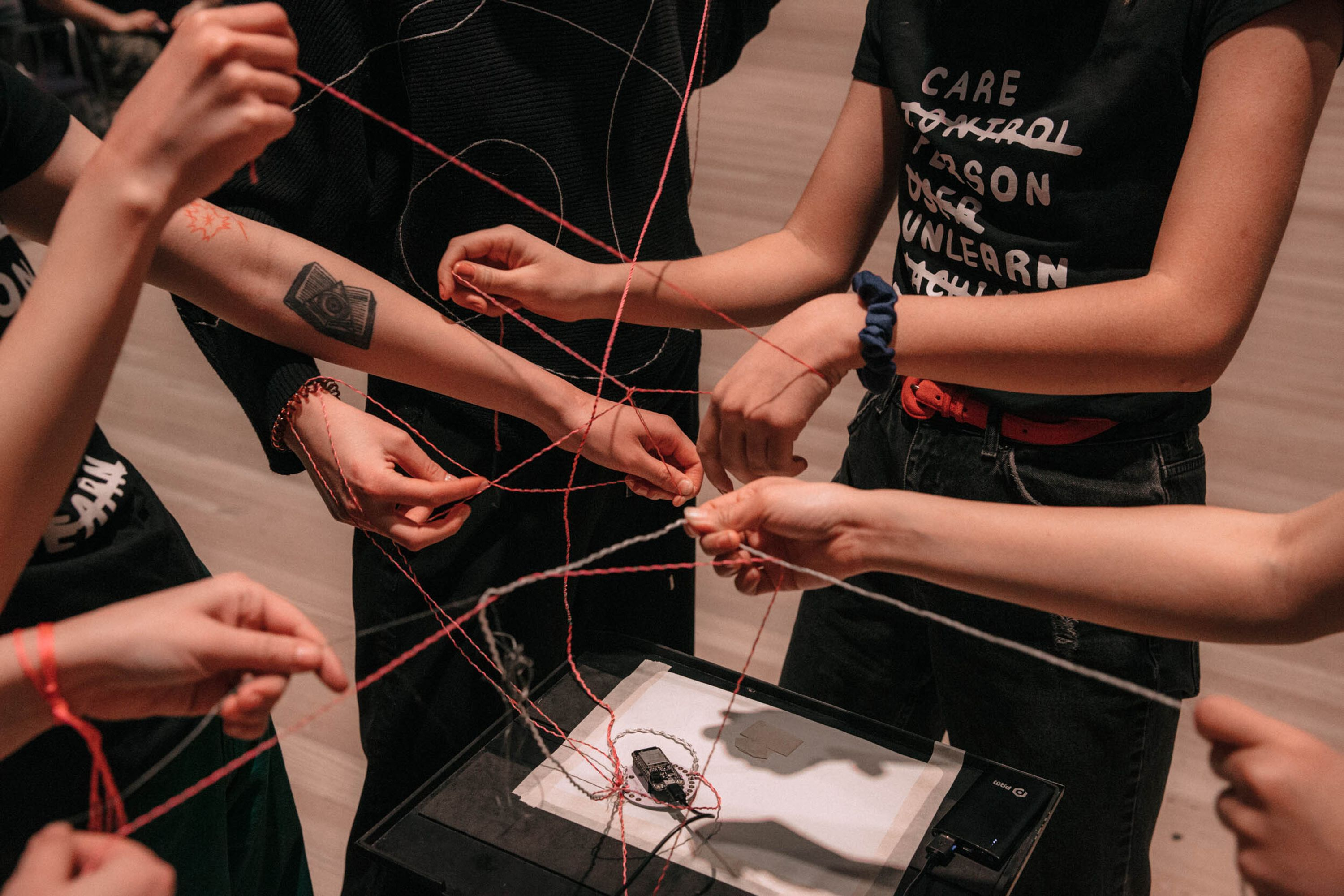 A group of hands holding different colored string that are all entangled with one another.