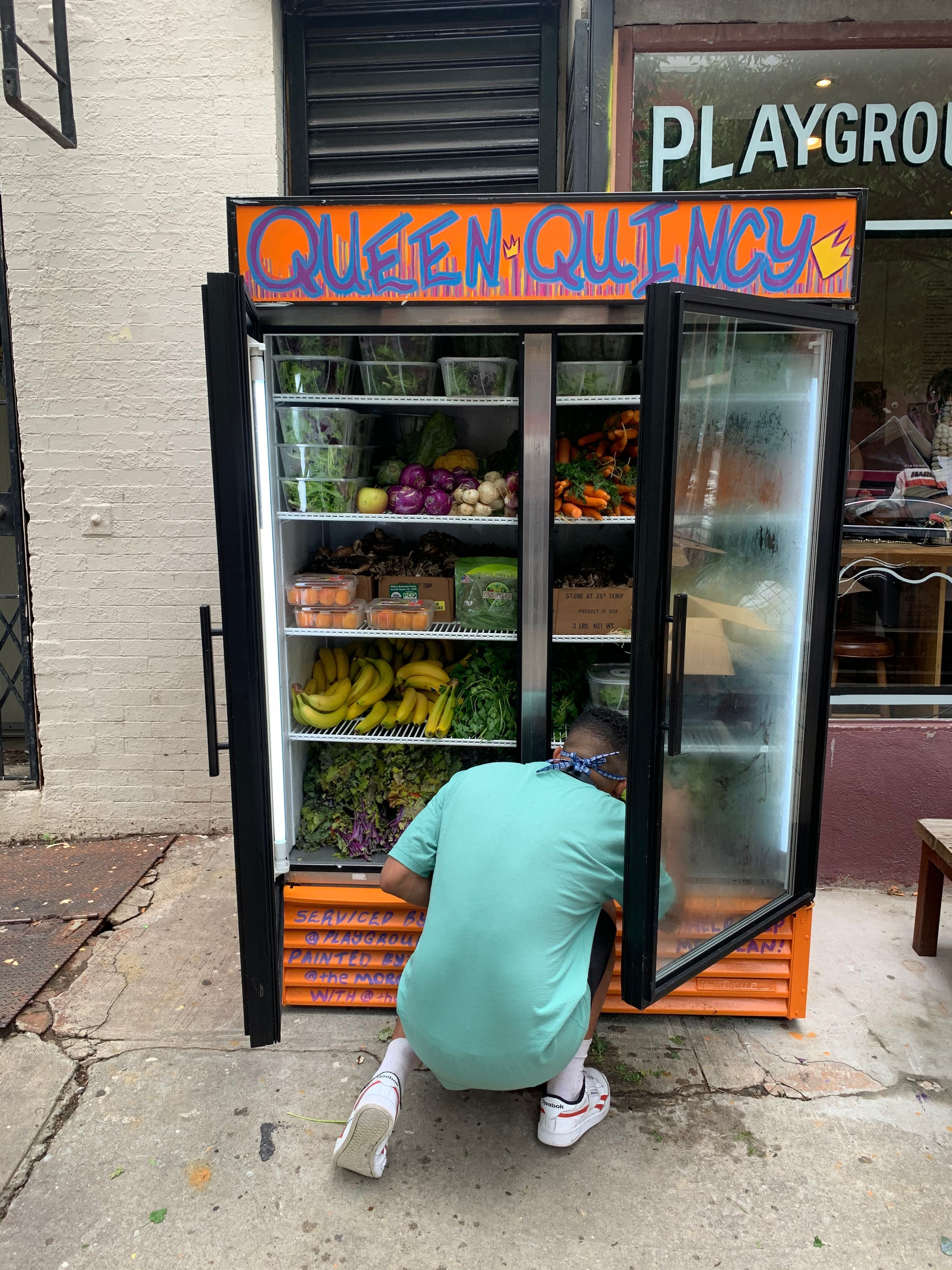 Edward Rivera filling the Community Fridge outside of Playground Coffee Shop.