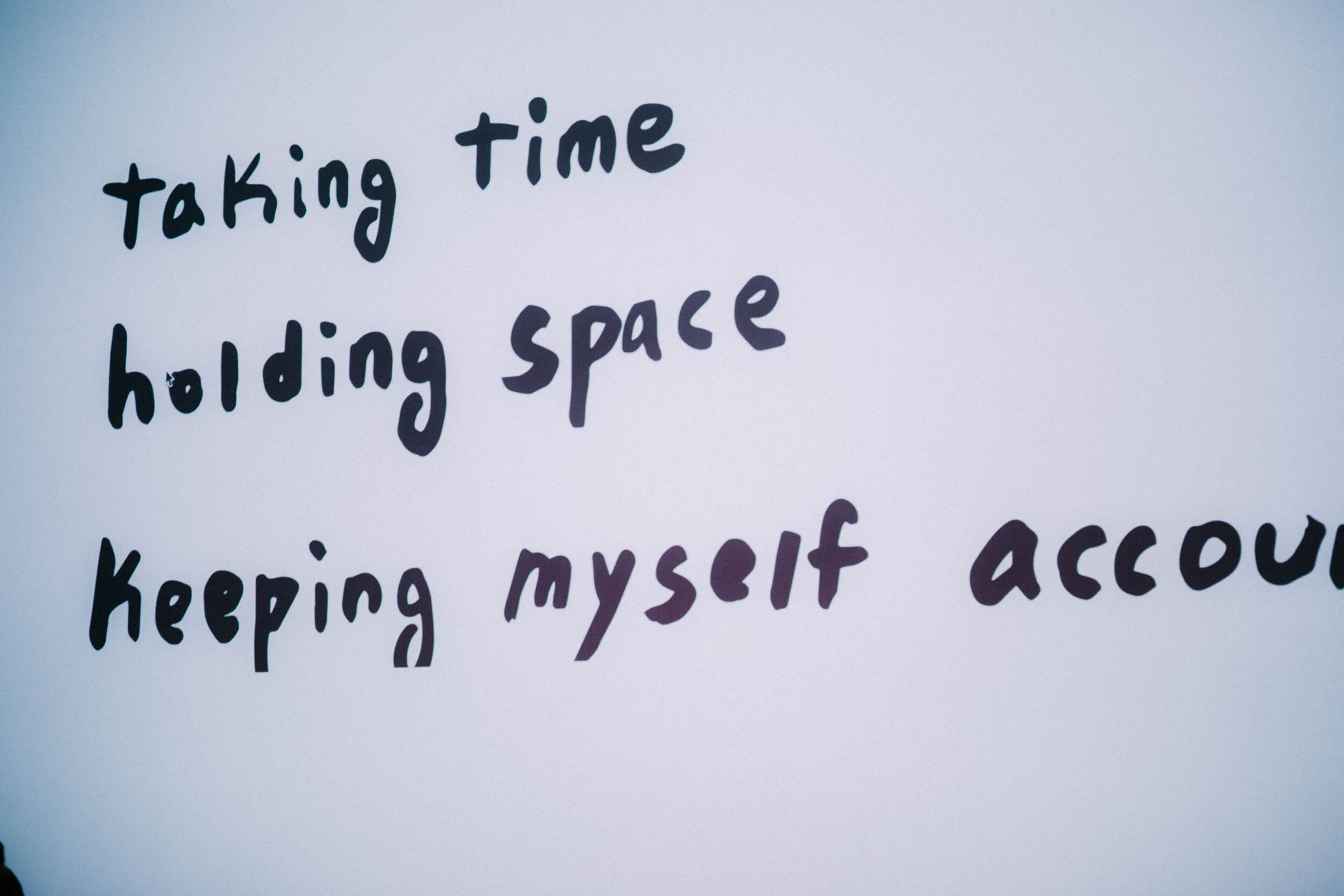 """Black writing on a grey background says, """"taking time, holding space, keeping myself accountable."""""""