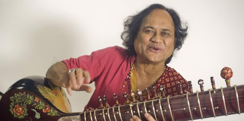 Khishna Mohan Bhatt, musician sitting and smiling