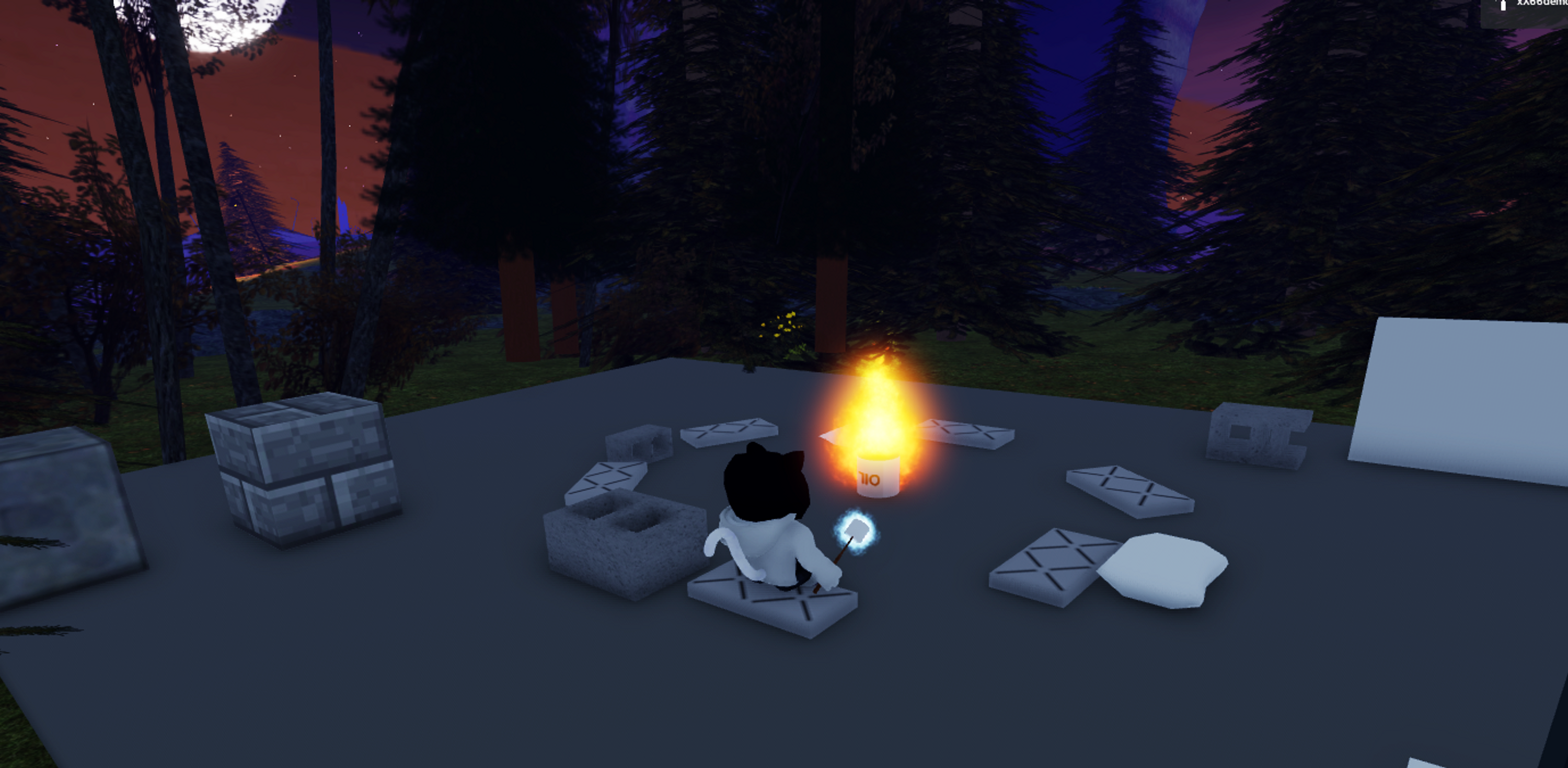 Screenshot of my avatar sitting at a fire in Roblox, holding a marshmallow, surrounded by the night sky with a big moon and dark trees.