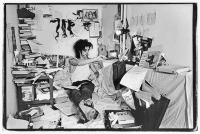 Nick Cave sits on the floor surrounded by books and papers