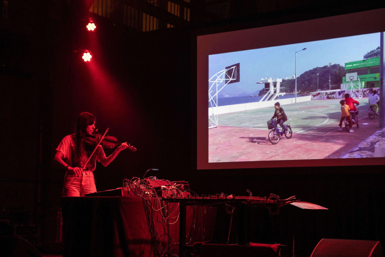 Hiro Kone playing violin onstage at Pioneer Works.