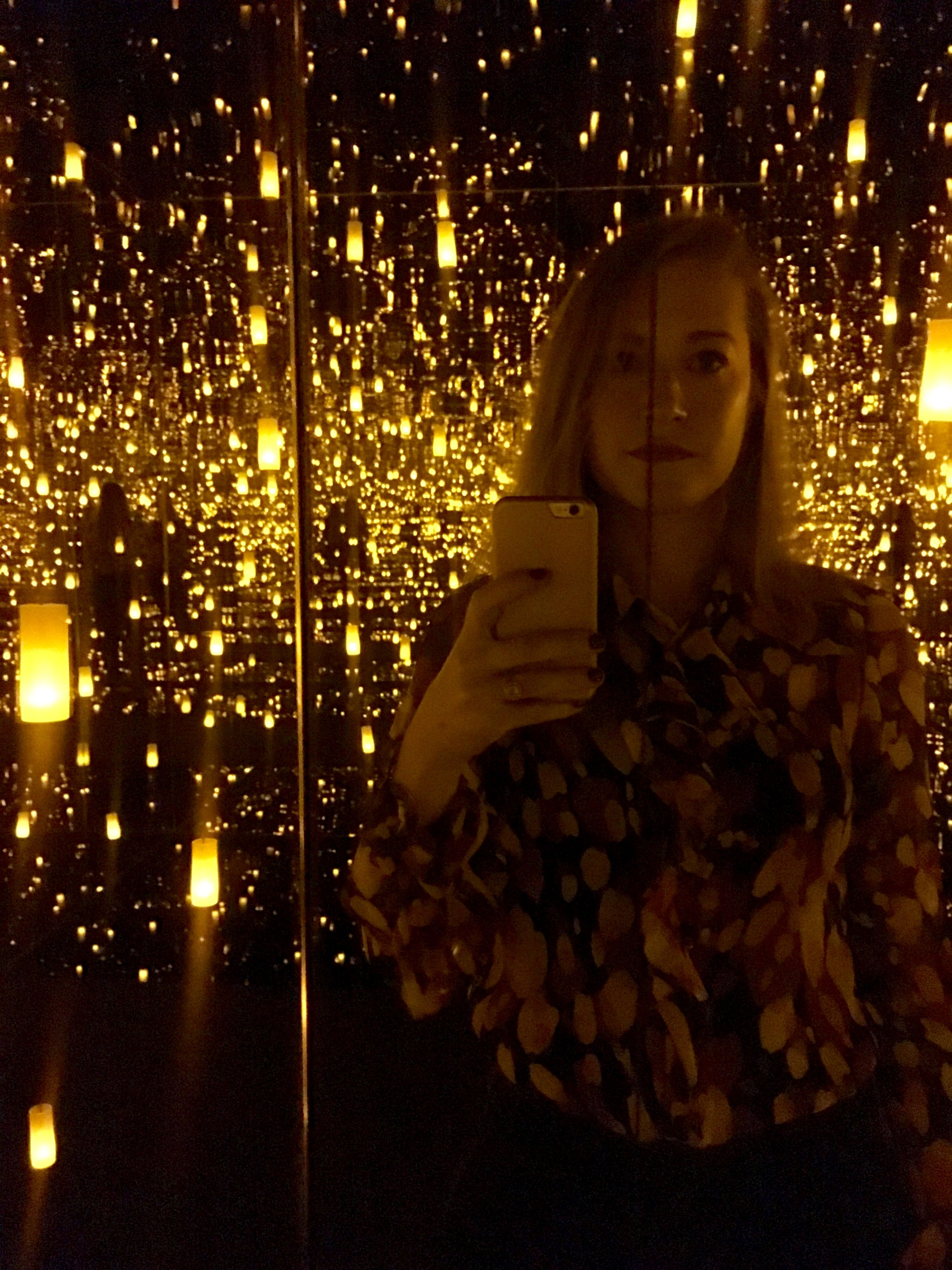 The author inside of a sparkle-filled installation by Yayoi Kusama