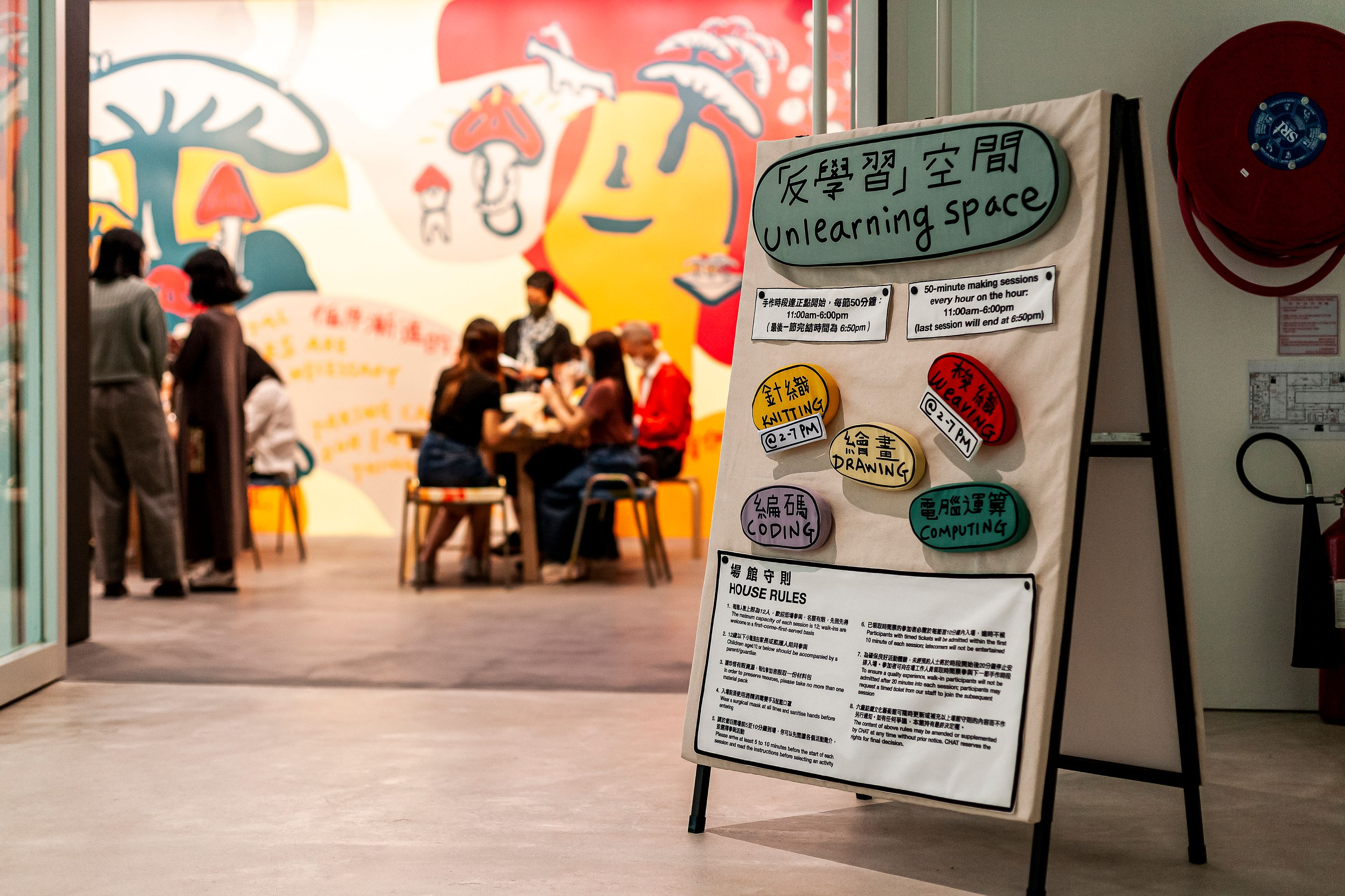"""In the foreground, a sandwich board sign says """"Unlearning Space,"""" and in the background, students gather at tables in a room that has a bright mural on the wall."""