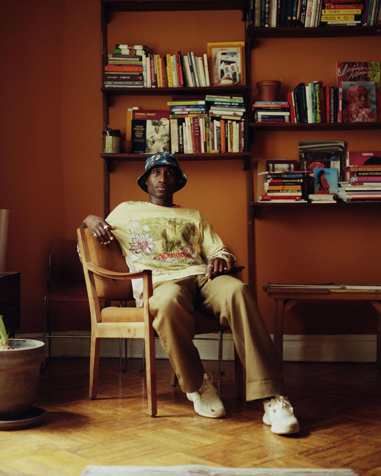 Devonn Francis sitting in front of bookshelves, wearing tan clothing and a blue bucket hat.