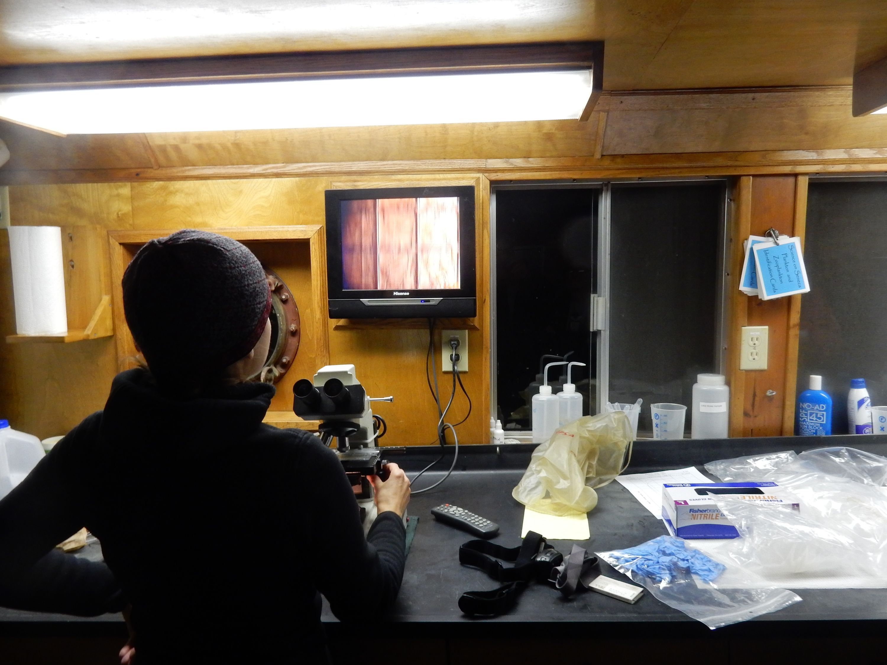 A woman dressed in black sits in front of a microscope.