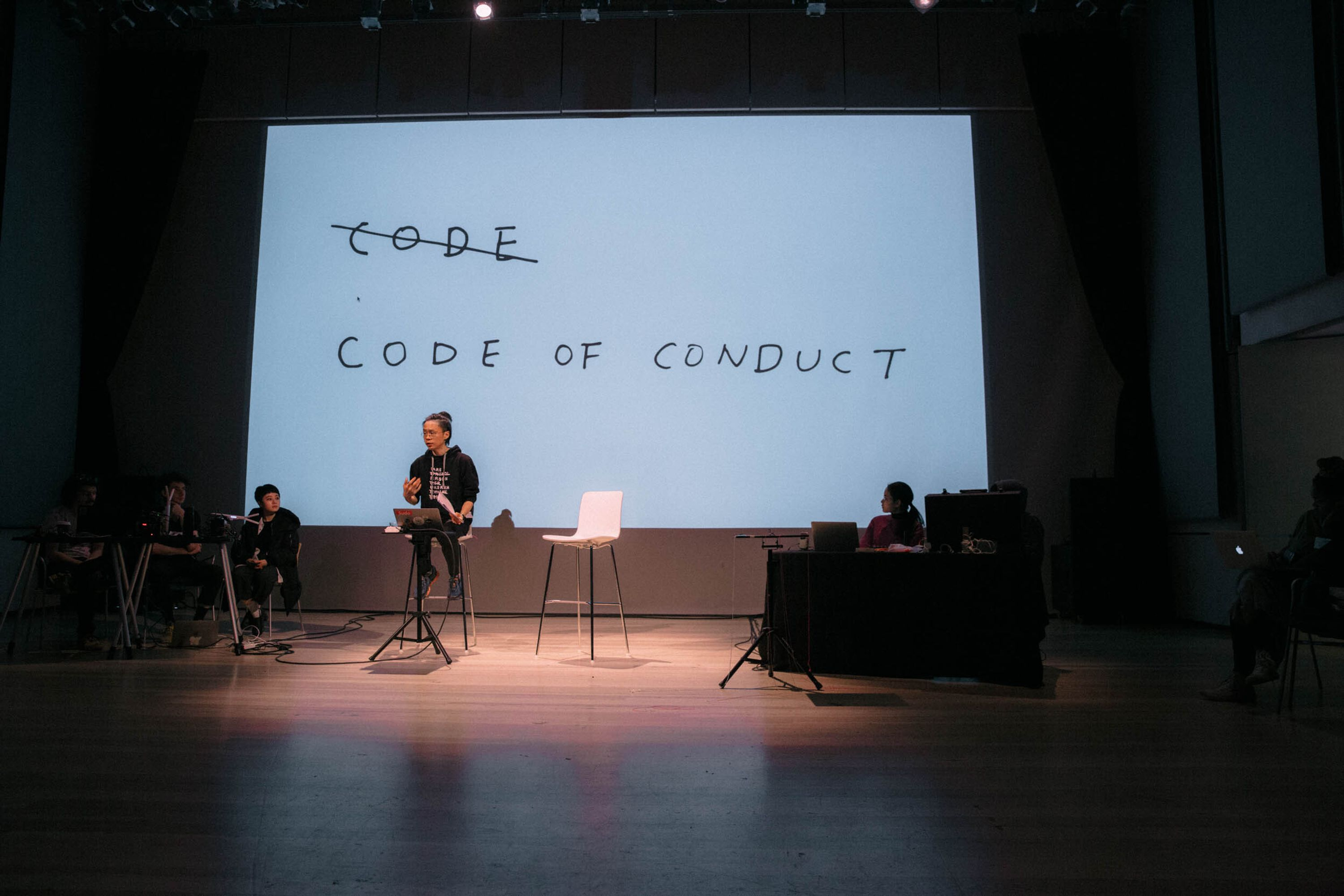 """Taeyoon is spotlit and wearing a black sweatshirt, sitting on a chair that's on a stage. Behind him, a large screen shows a handwritten images where the word """"code"""" is crossed out, and """"code of conduct"""" is written below."""