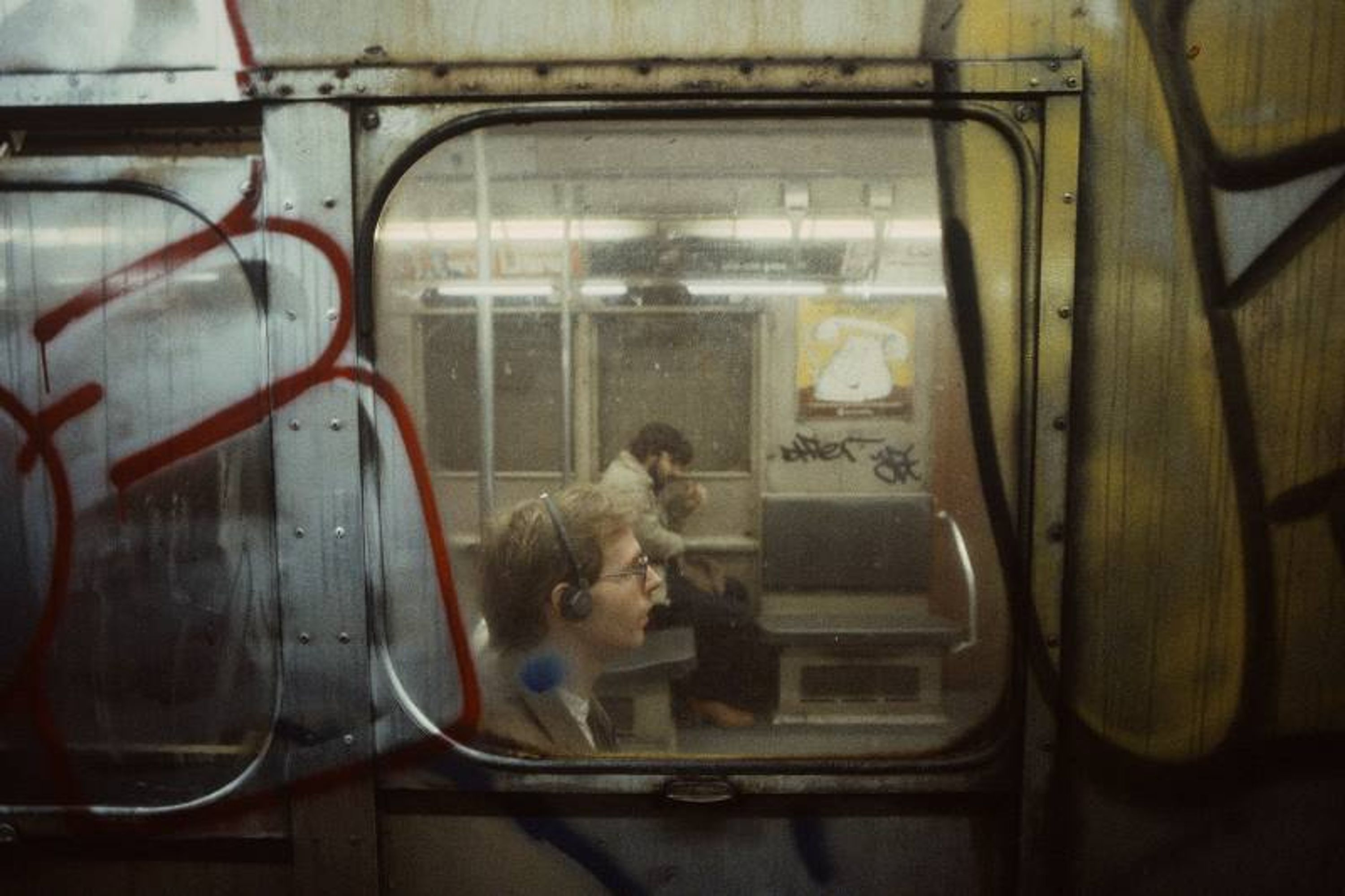 Photo from the subway of a person in another subway car listening to a walkman.