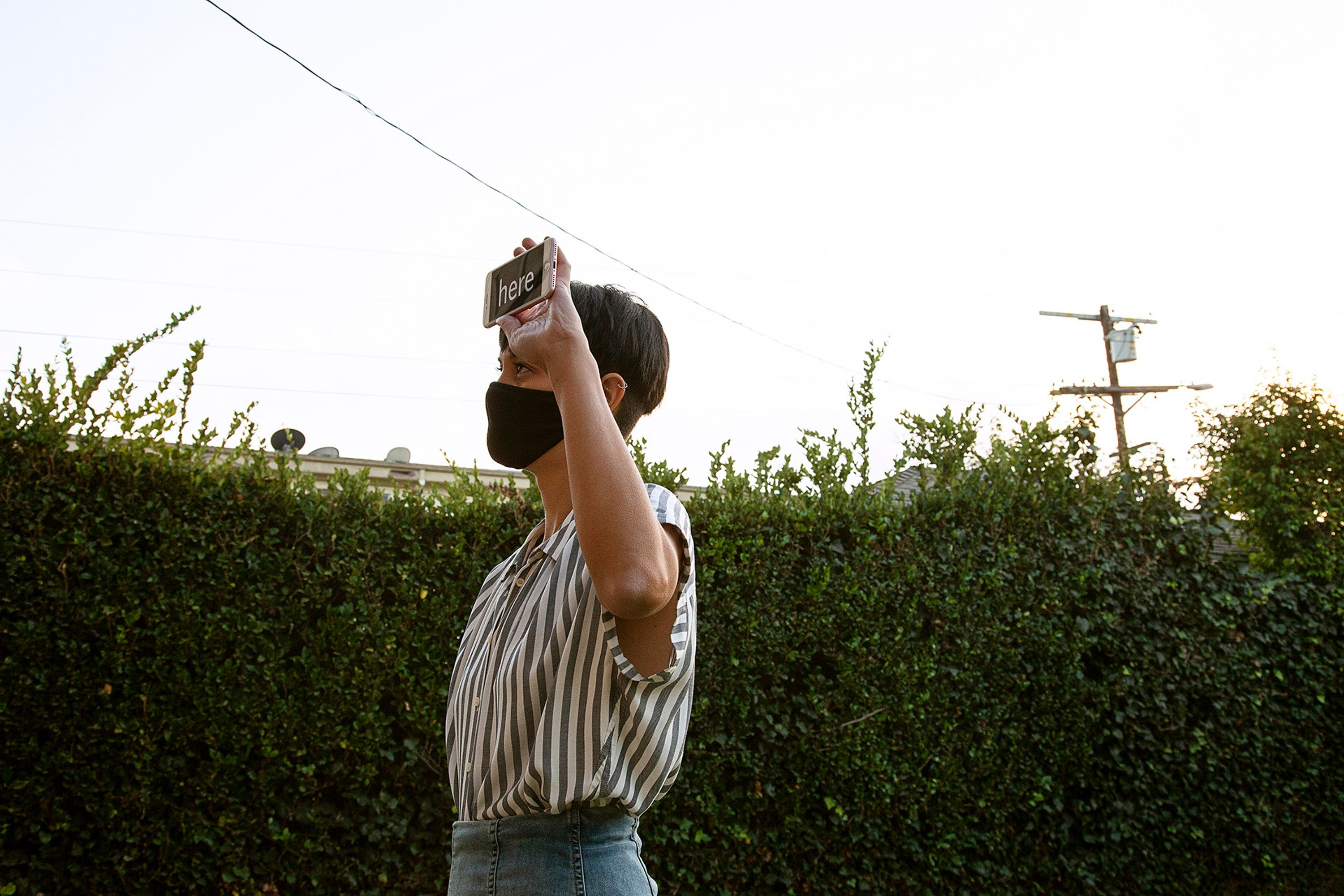 """The artist stands in front of a green hedge holding up here smartphone, which has the word """"here"""" shown on its screen in white text over a black background. She wears a black mask and a white and grey striped shirt."""