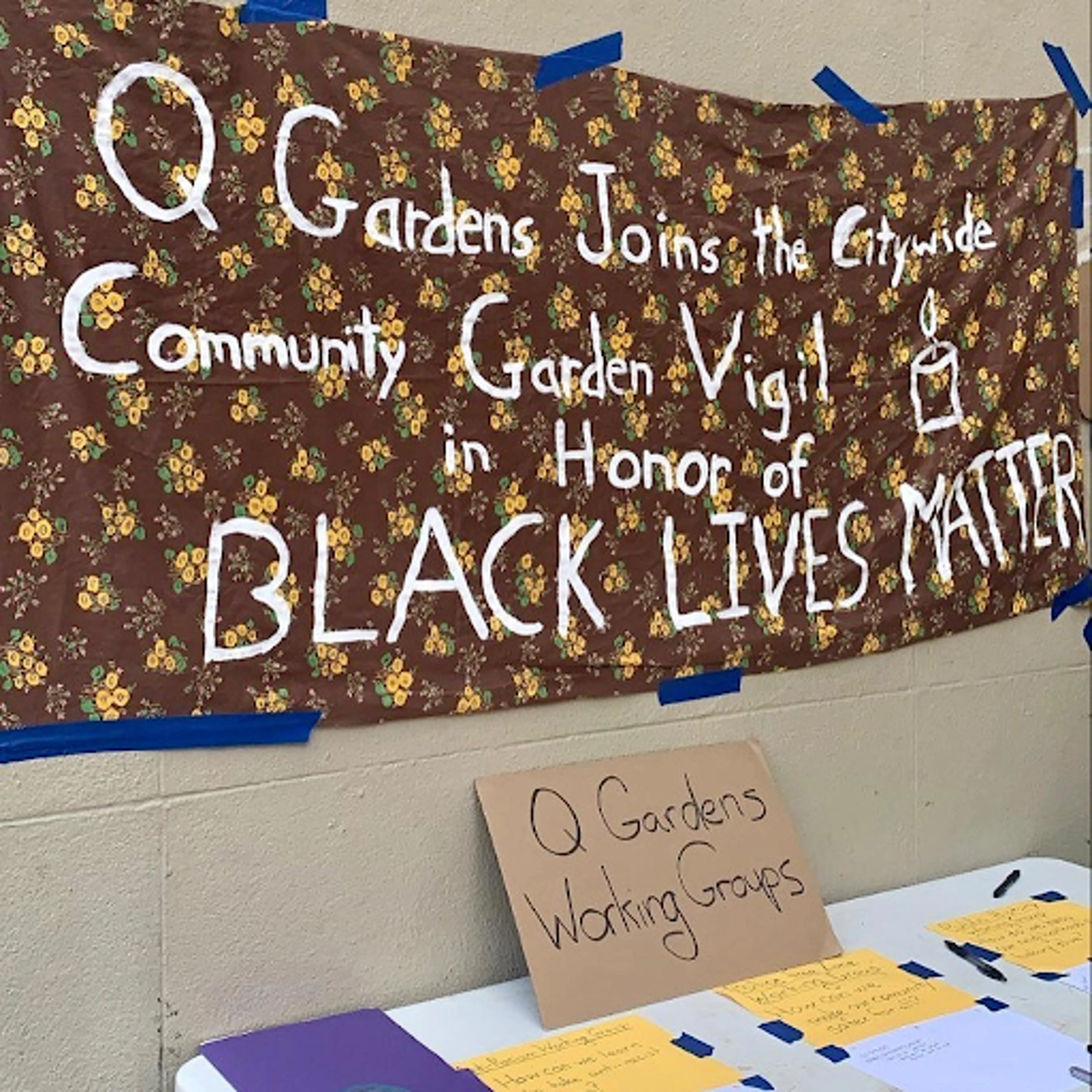 """Banner saying """"Q Gardens joins the citywide community garden vigil in honor of Black Lives Matter."""""""