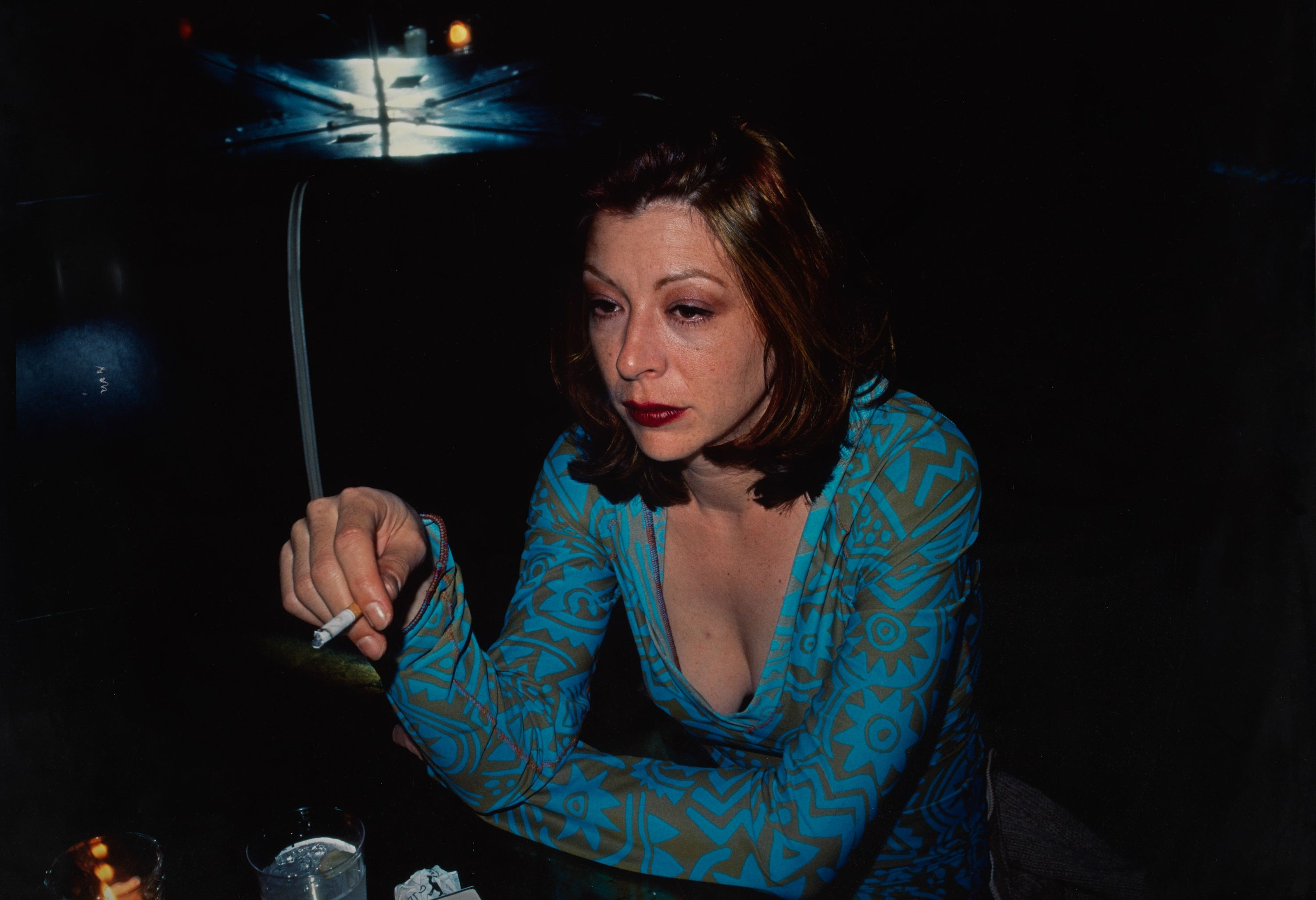 A photograph of Kathleen White sitting at a bar, gazing in the distance looking sad