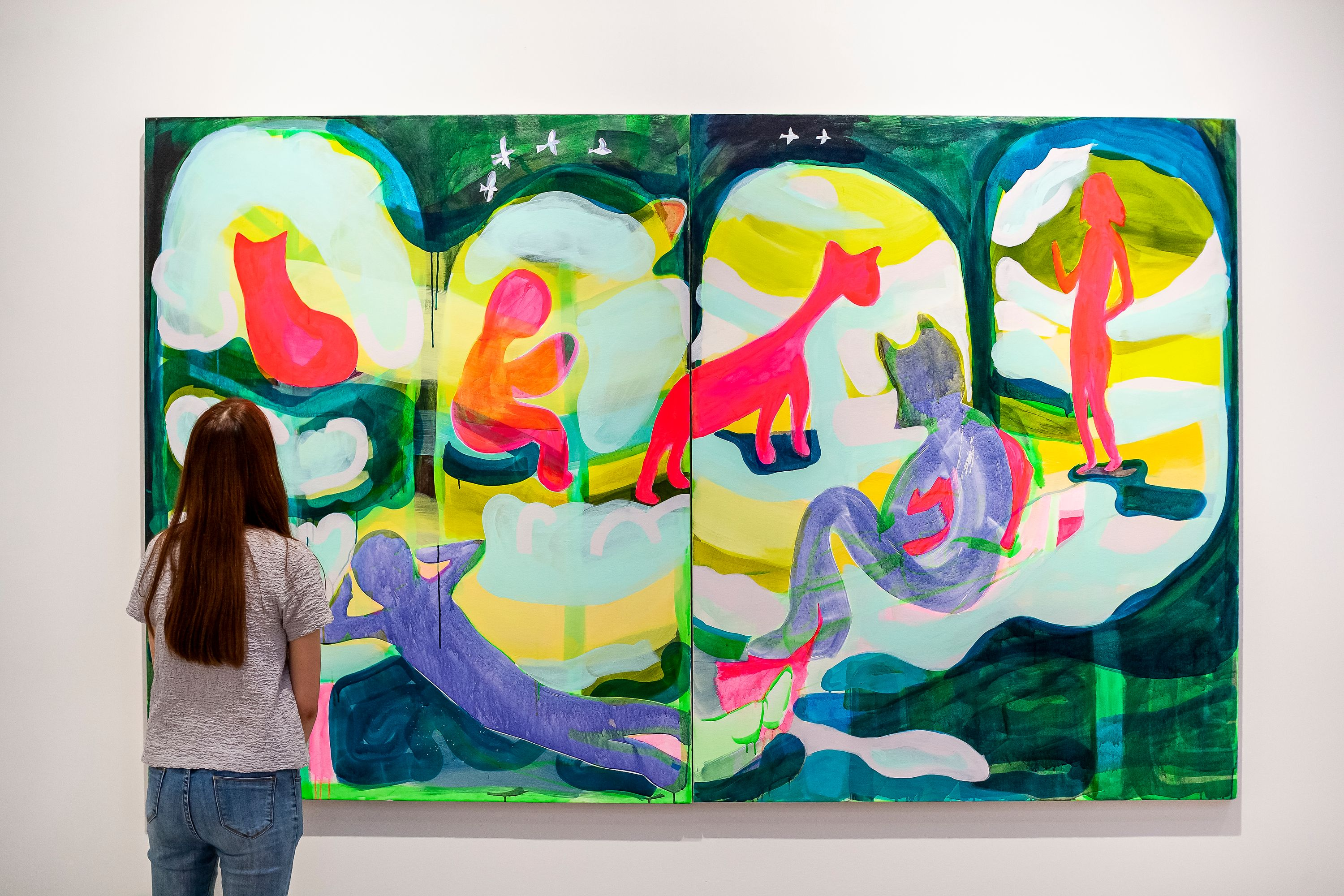 A woman with long brown hair stands facing a large painting by Taeyoon, hung on a white gallery wall. The painting is colorful, with ping cat-like and human-like forms and a flowing background painted in dark greens, light teals, and purple.