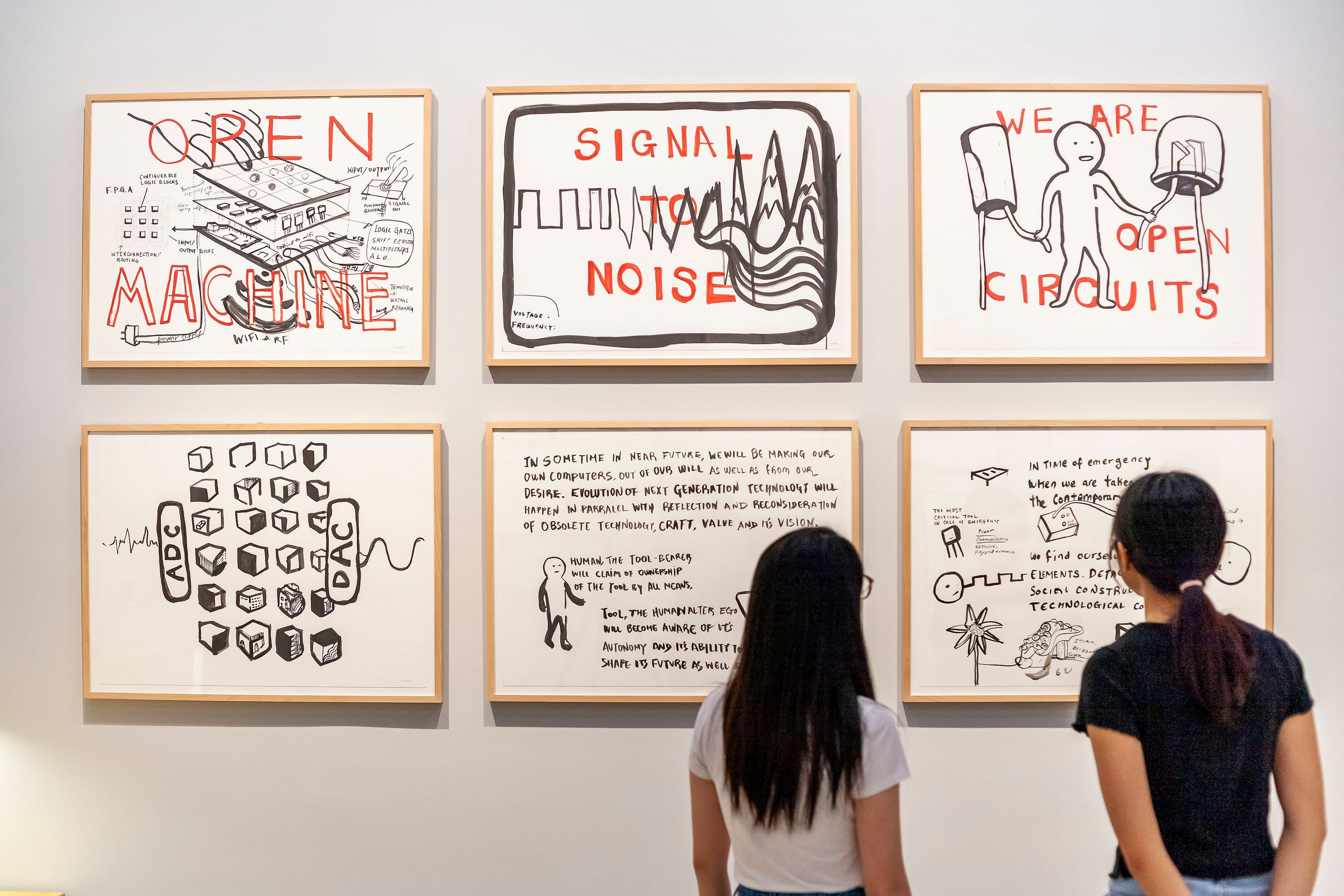 """Two women, both with long brown hair, stand with their backs to the camera. They are looking at Taeyoon's art hanging on a gallery wall. One artwork says """"OPEN MACHINE"""" and shows technical drawings, another says """"WE ARE OPEN CIRCUITS"""" and depicts a simple character connecting two nodes."""