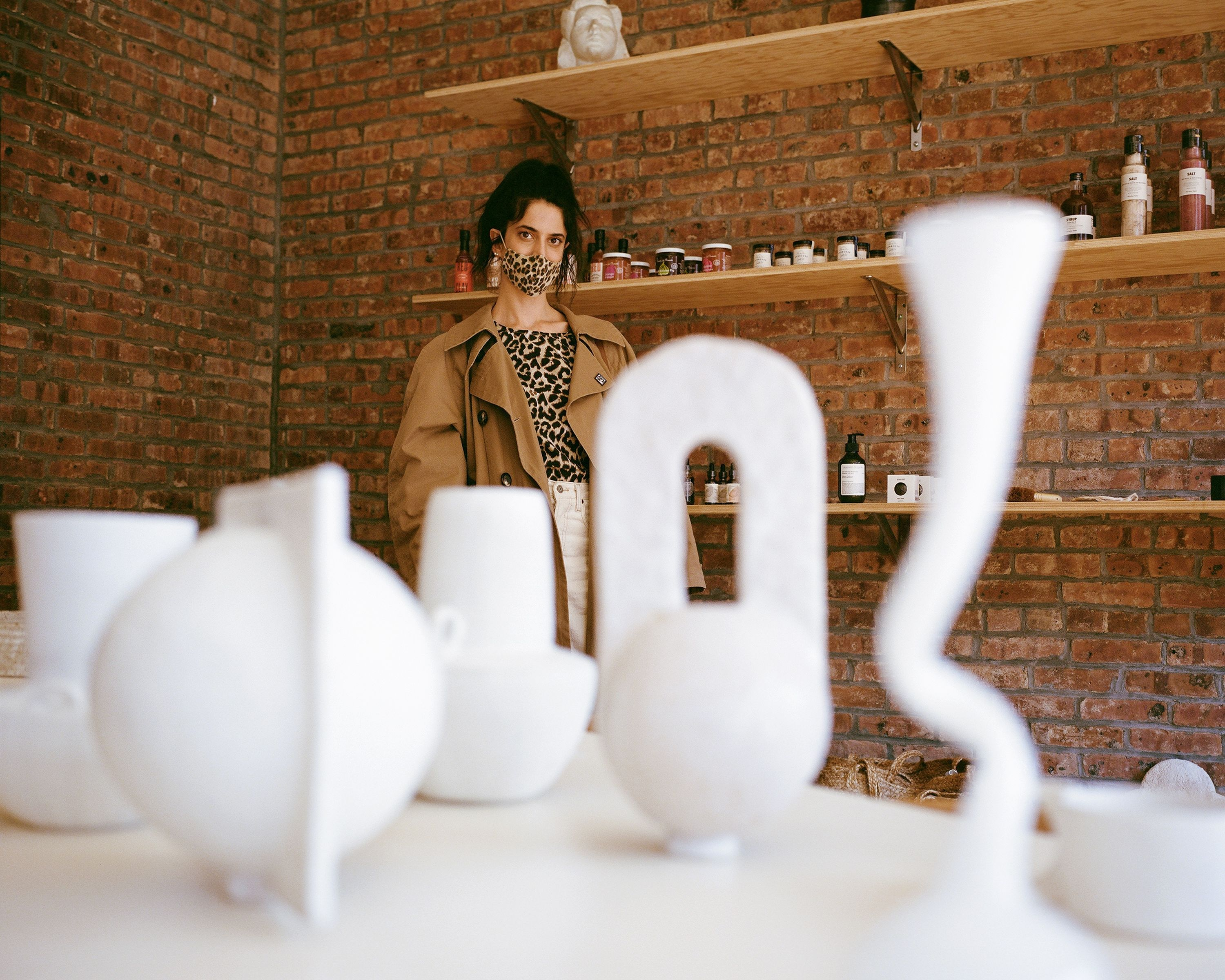 Anna Polonsky posing in front of sculptural vases at Raini Home in bedford-stuyvesant