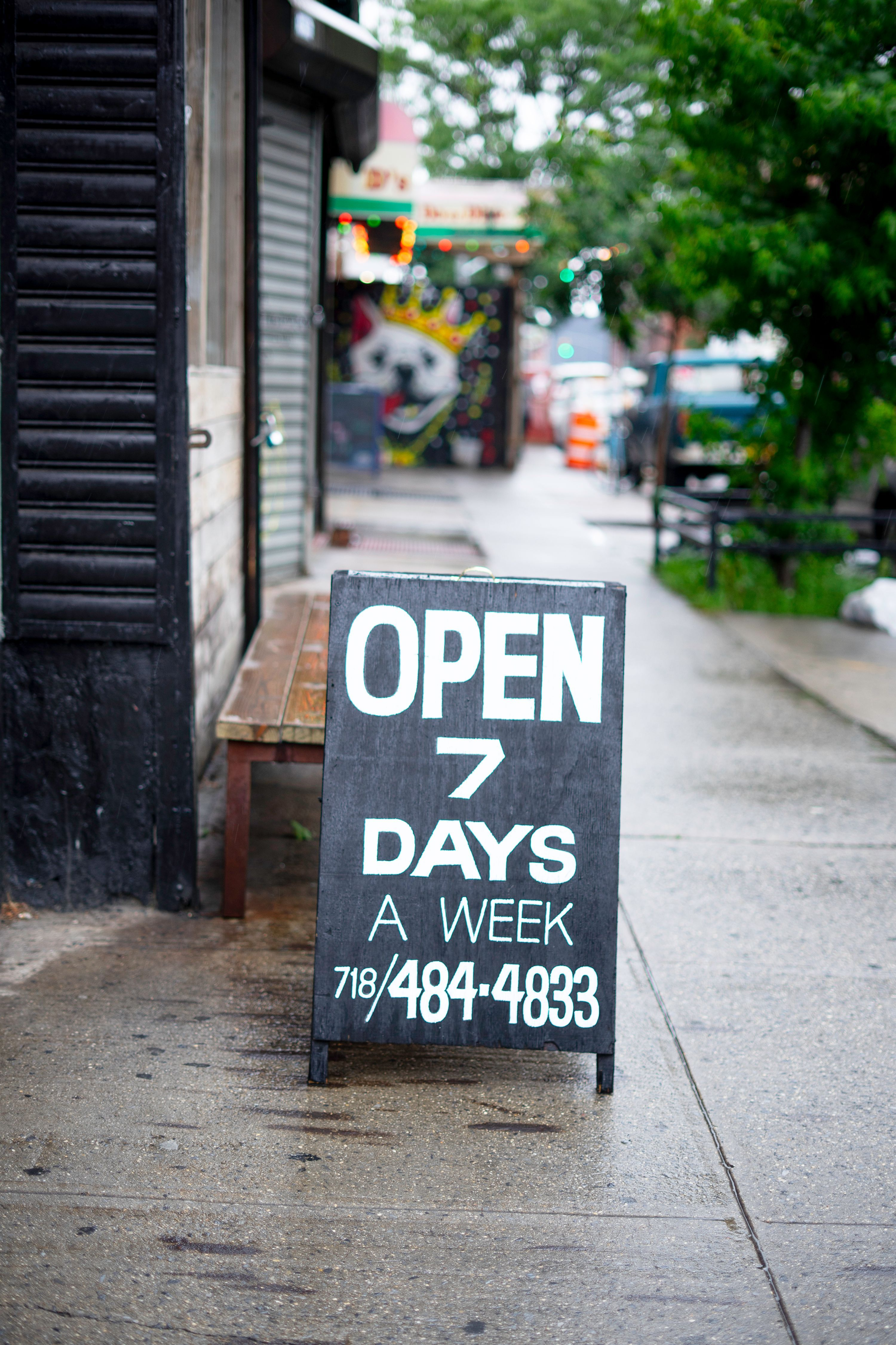 """""""Open 7 Days A Week"""" sign outside of the Playground Coffee Shop entrance."""