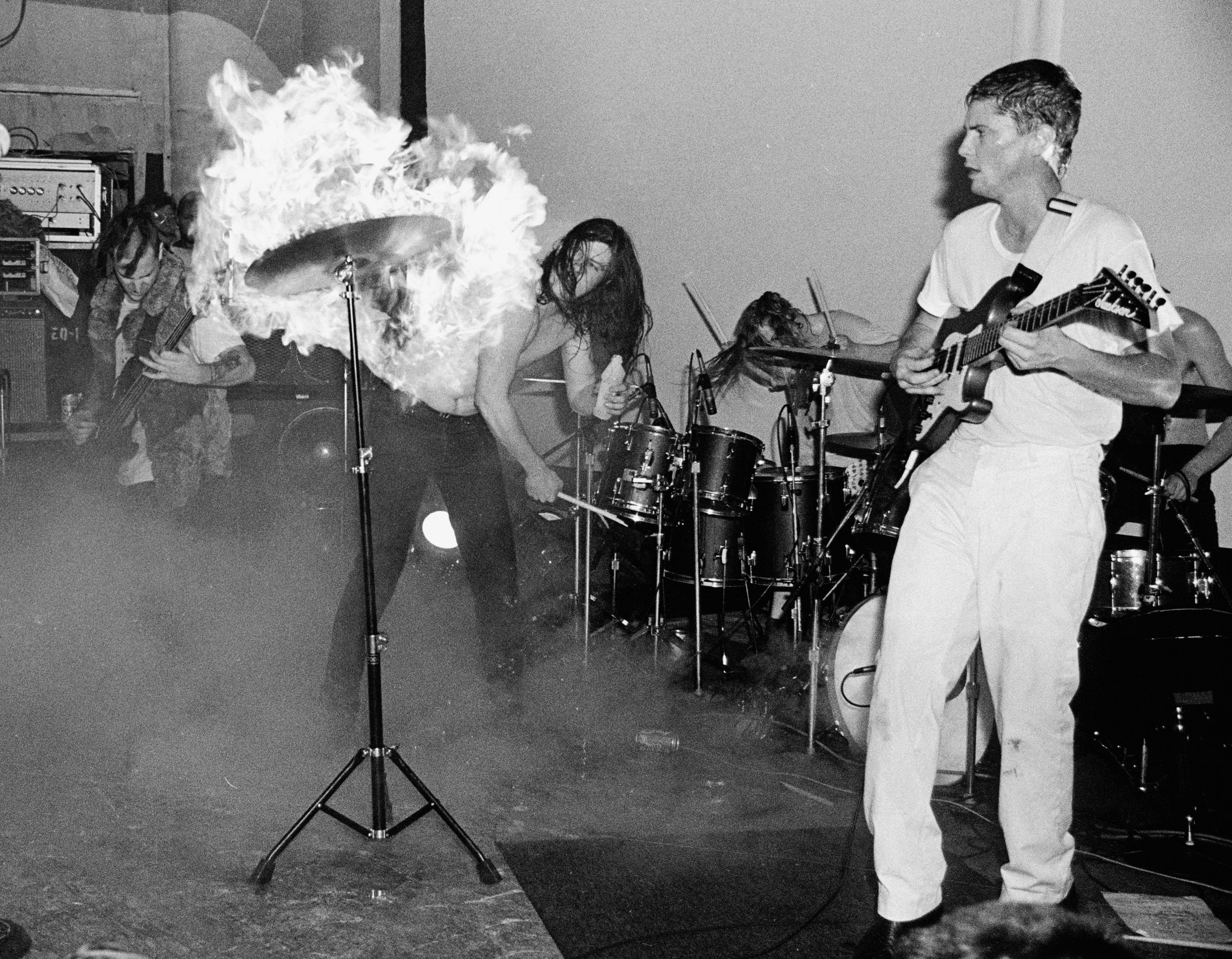 Gibby Haynes hitting a flaming cymbal with a drum stick while his band plays