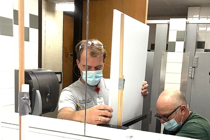 Facilities Operations team members install a partition in a restroom