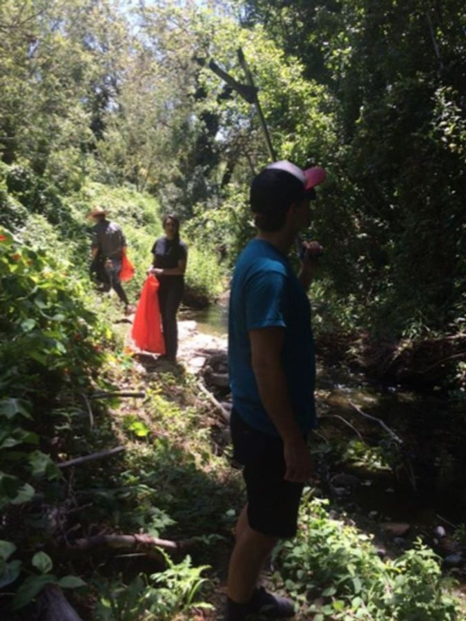 Student volunteers search local creeks for trash and debris.