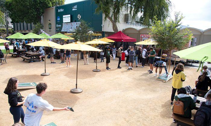 Guests playing cornhole and visiting food trucks.