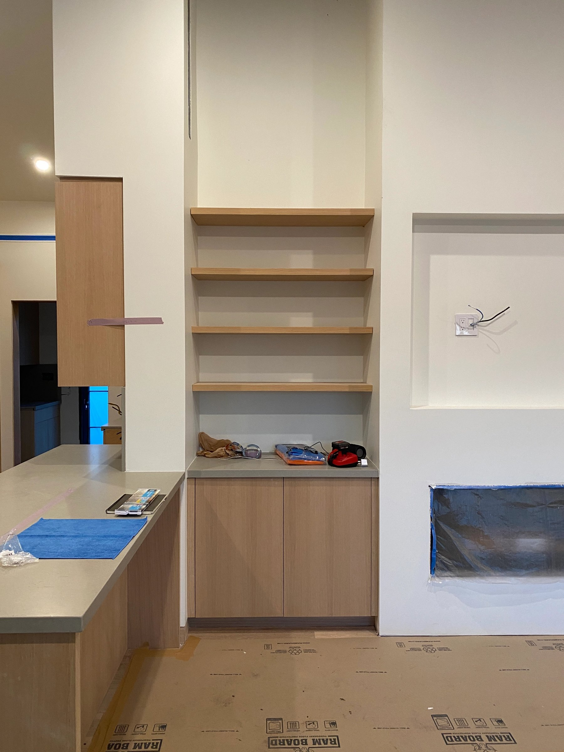 Built-in white oak shelving next to the fireplace