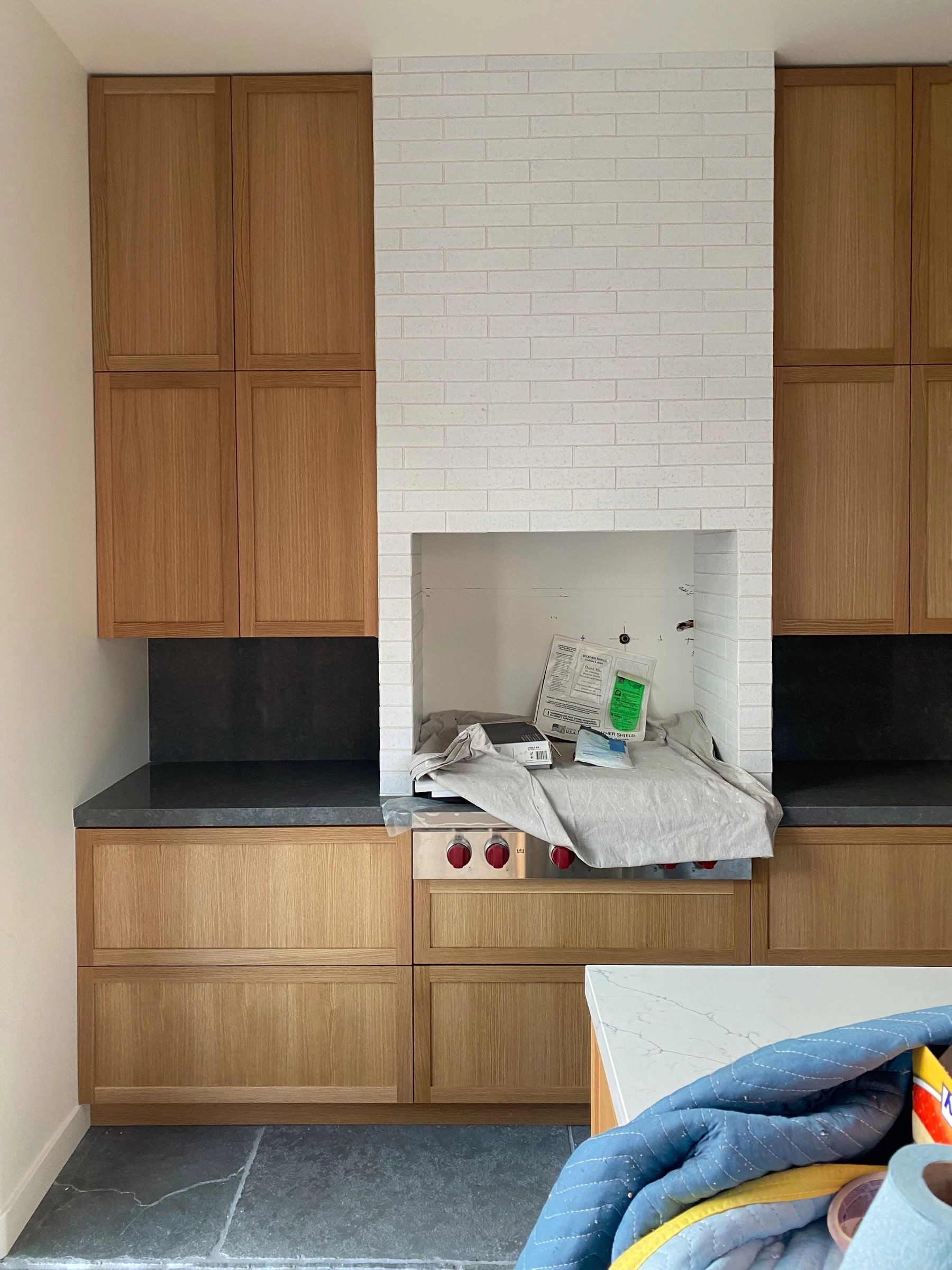A built in range and hood clad in brick