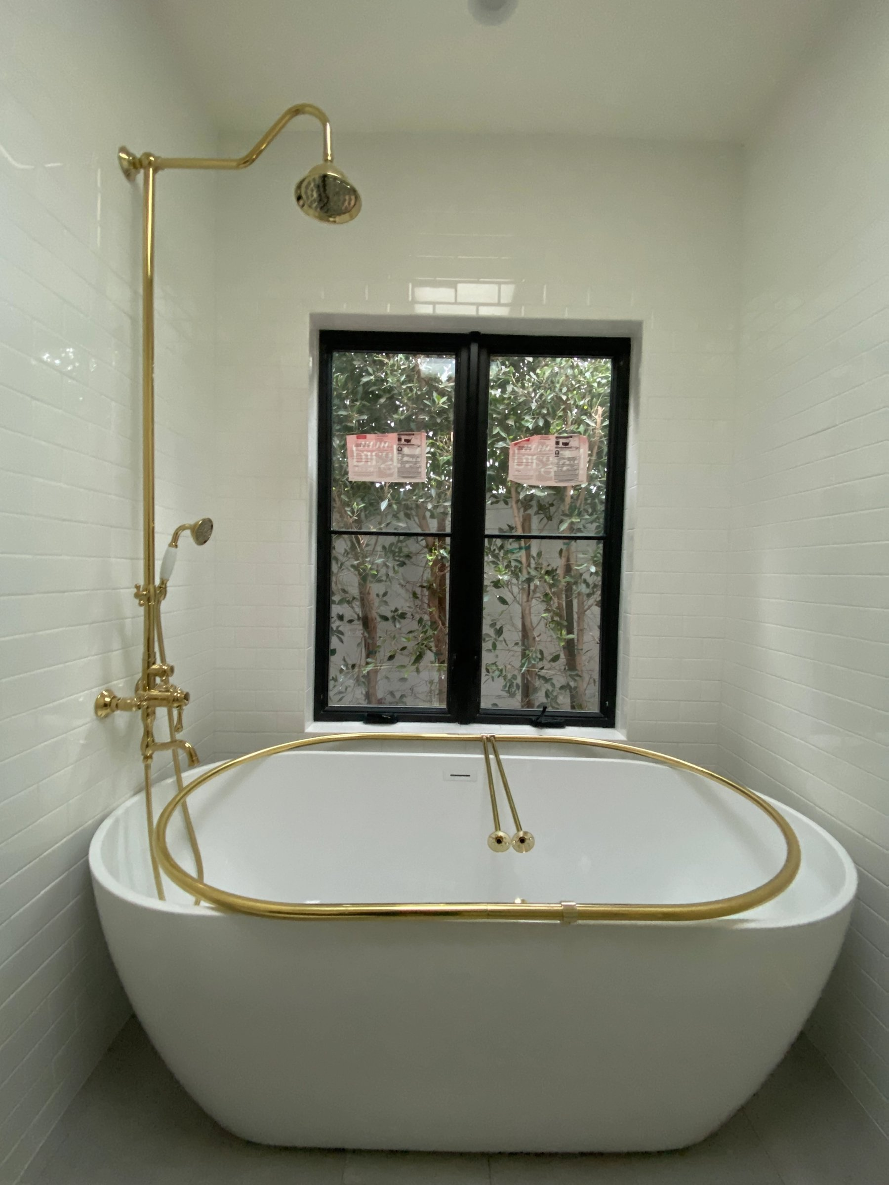 A free-standing soaking tub with a classic shower kit and oval curtain rod