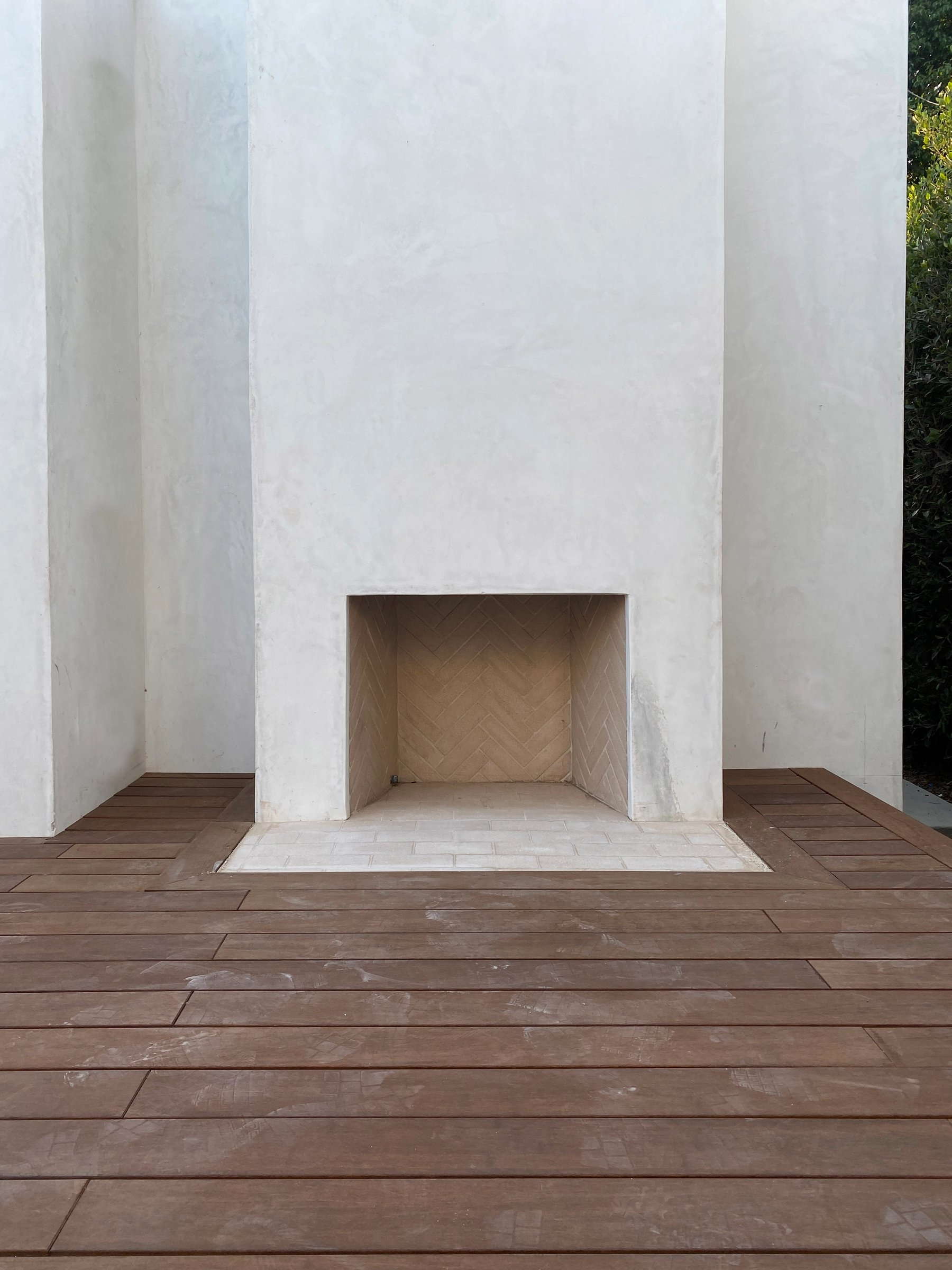 An outdoor fireplace clad in smooth stucco with a sustainable bamboo deck