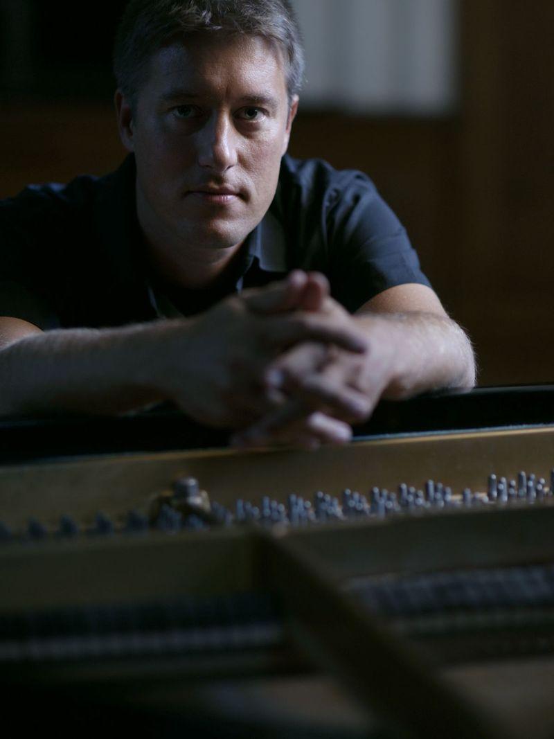 Lars David Kellner am offenen Piano in die Kamera blickend