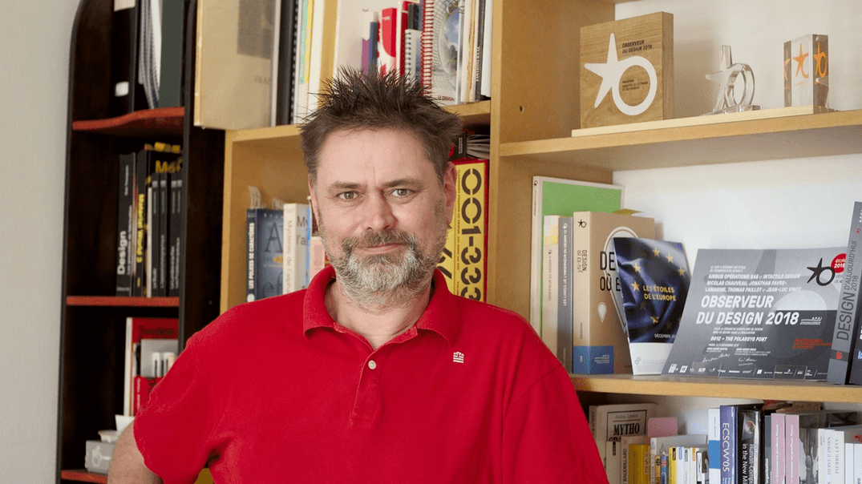 Portrait d'Yves Rinato devant les Étoiles du design qui ont récompensées l'agence intactile