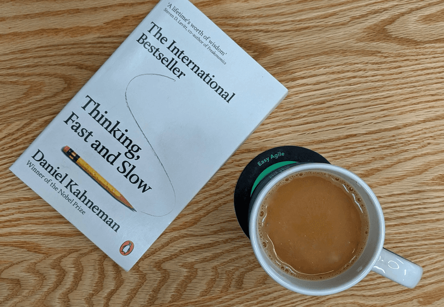 Copy of Daniel Kahneman's book 'Thinking, Fast and Slow' and coffee cup on table