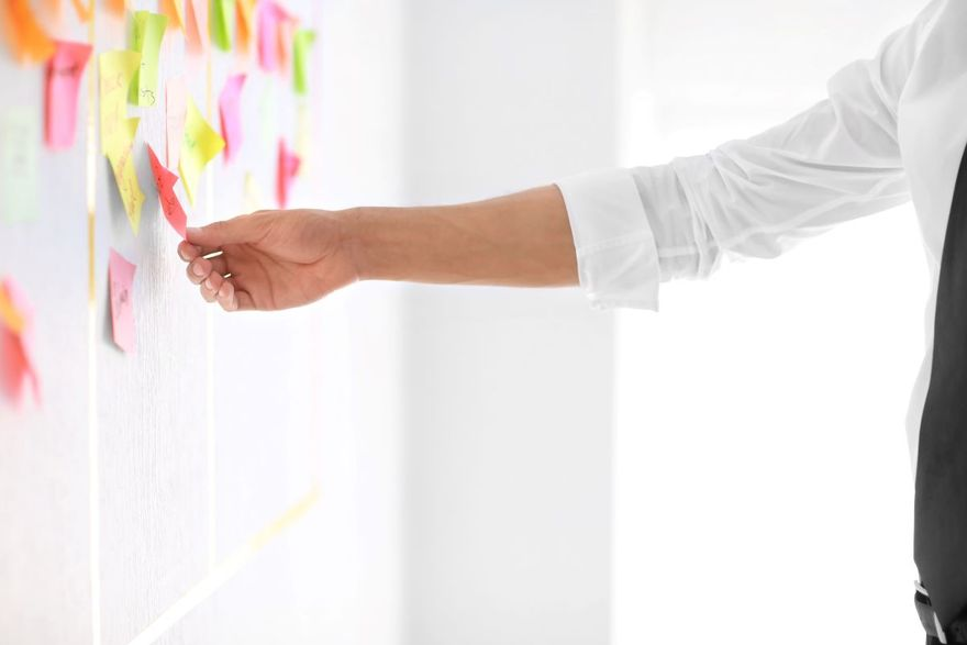Man looks at a post-it on a program board