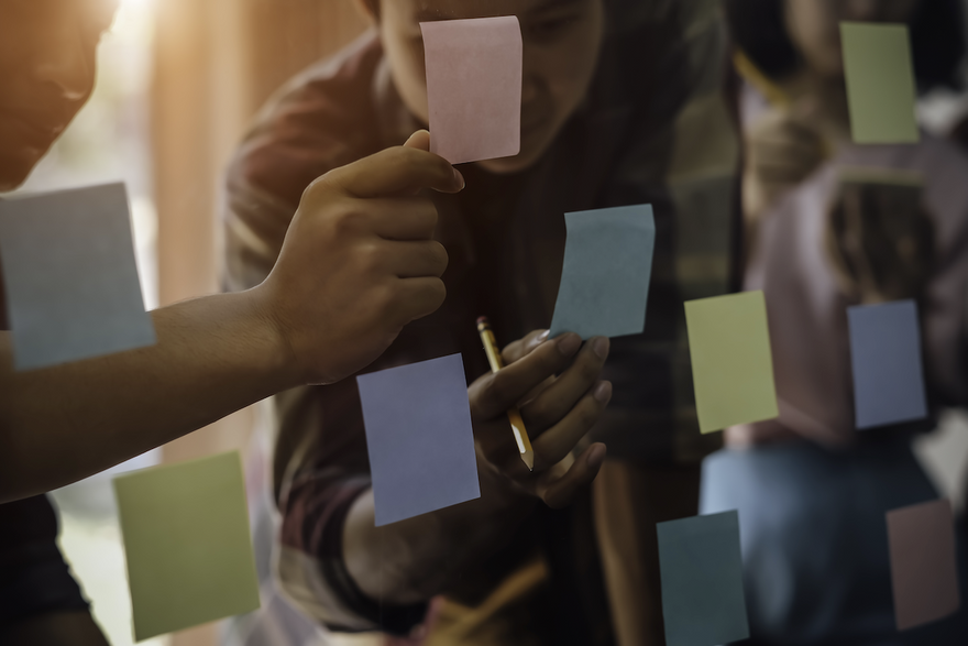 affinity mapping: men looking at the sticky notes