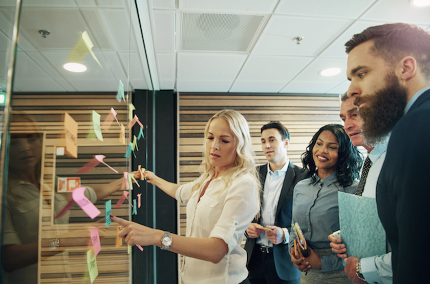 product management framework: woman showing sticky notes to her co workers