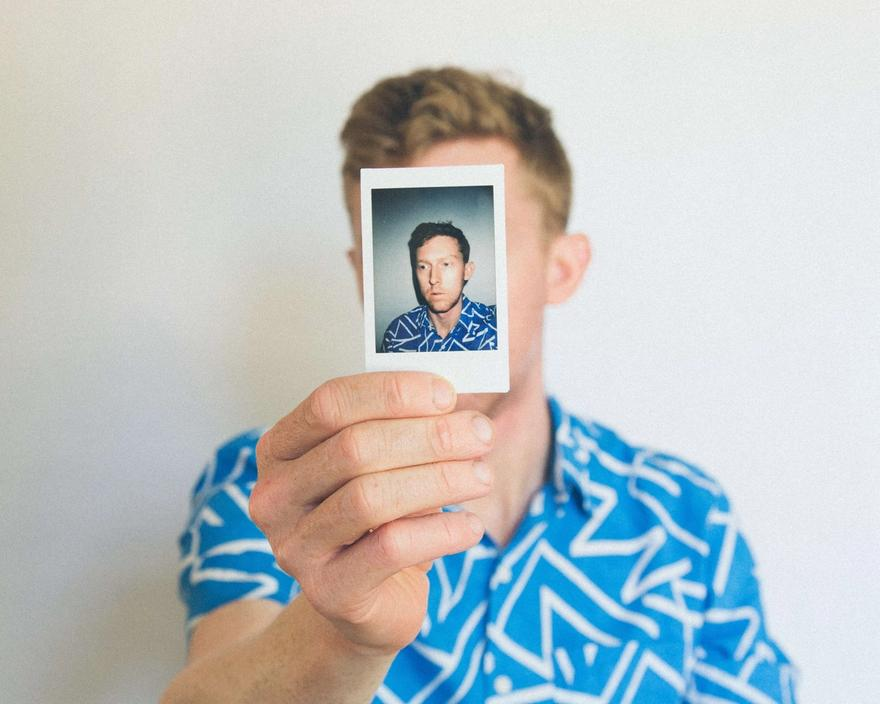 Man in a blue patterned shirt holds a portrait photo of himself in front of his face.