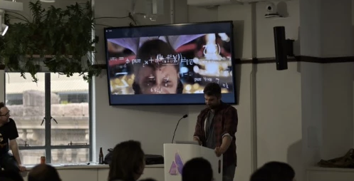 A person standing in front of a screen presenting to an audience.