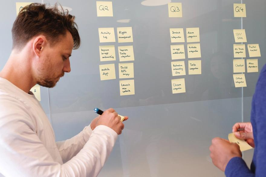Jira project management: Group of people looking at sticky notes