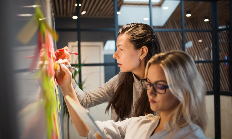 Agile transformation: two women writing on a whiteboard
