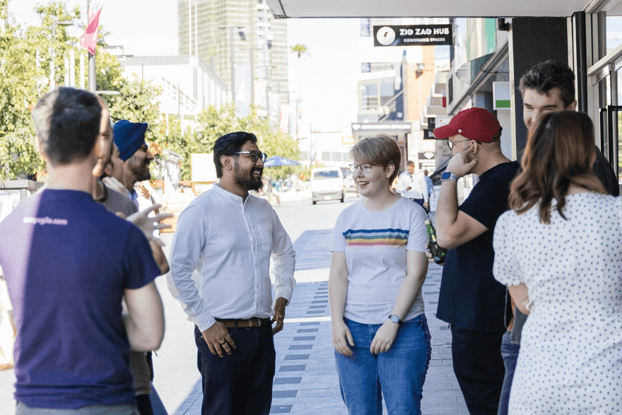 Team chatting outside morning coffee