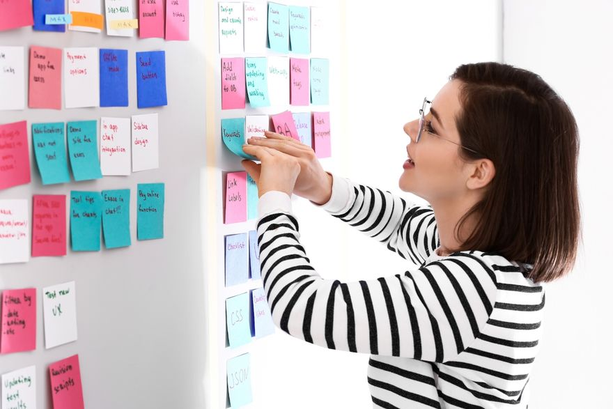 software development methodologies: Woman posting sticky notes on the office board