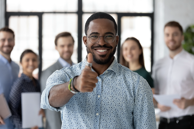 agile estimation: man giving a thumbs up while smiling with people in the background