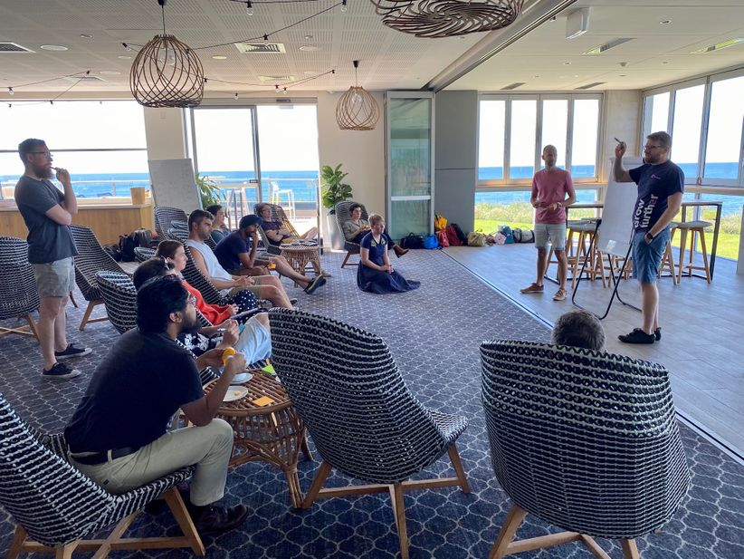 Two people presenting to a group sitting around them with an ocean backdrop.