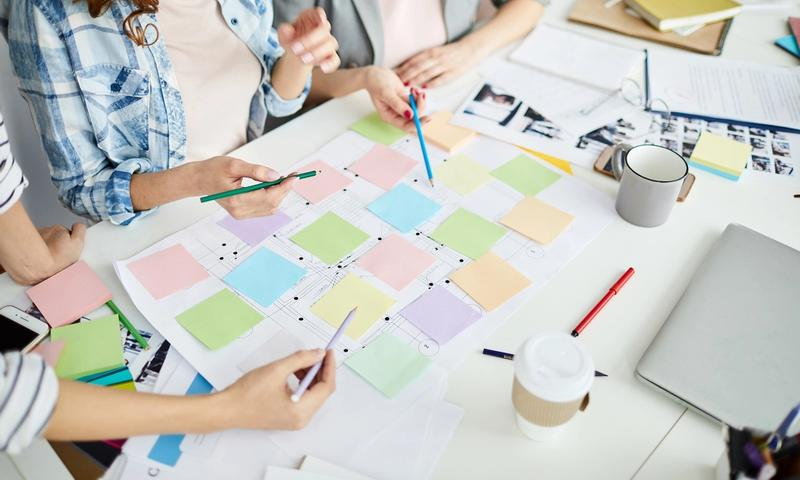 Jira roadmap: Team of employees brainstorming using sticky notes